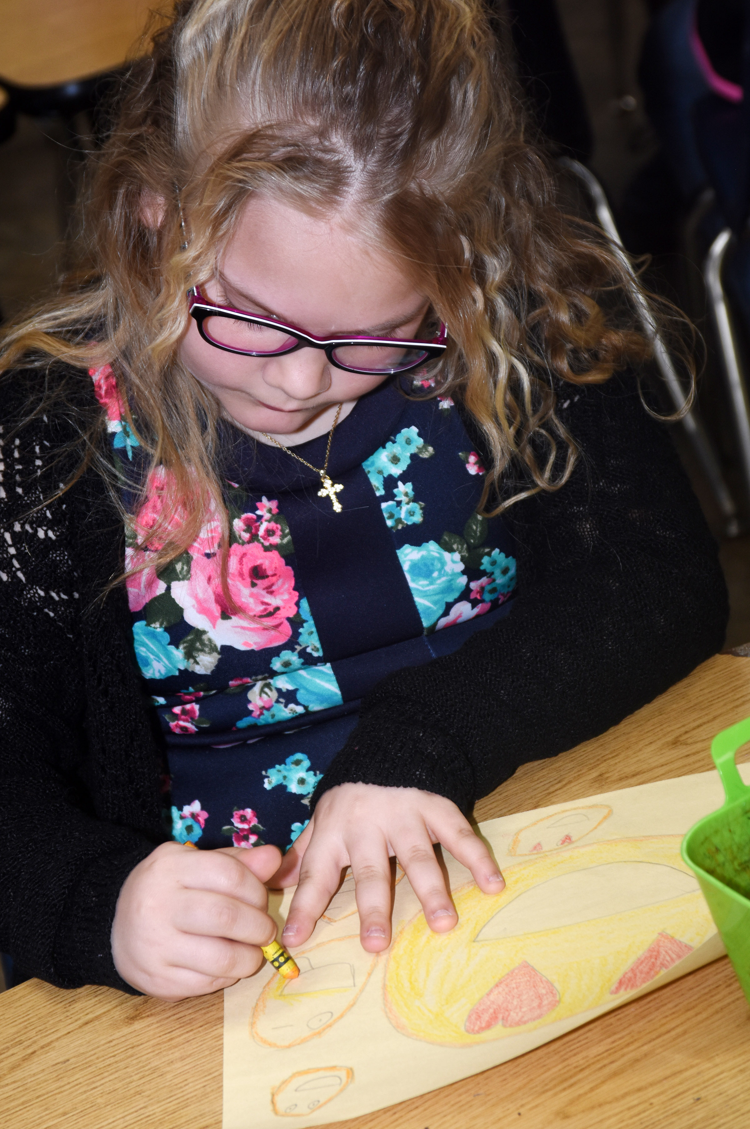 CES second-grader Addysen England colors a drawing she created to make someone smile.