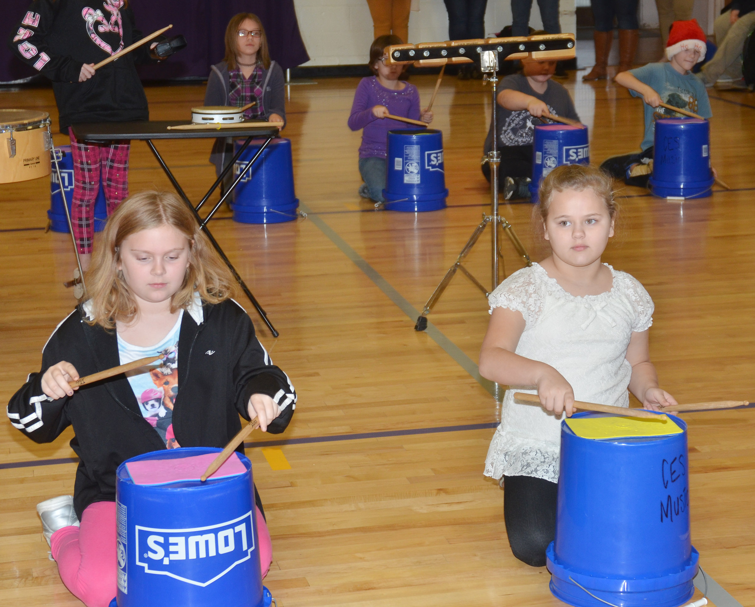 CES fourth-graders Arianna Childers, at left, and Amaya Anguiano play the bucket drums.