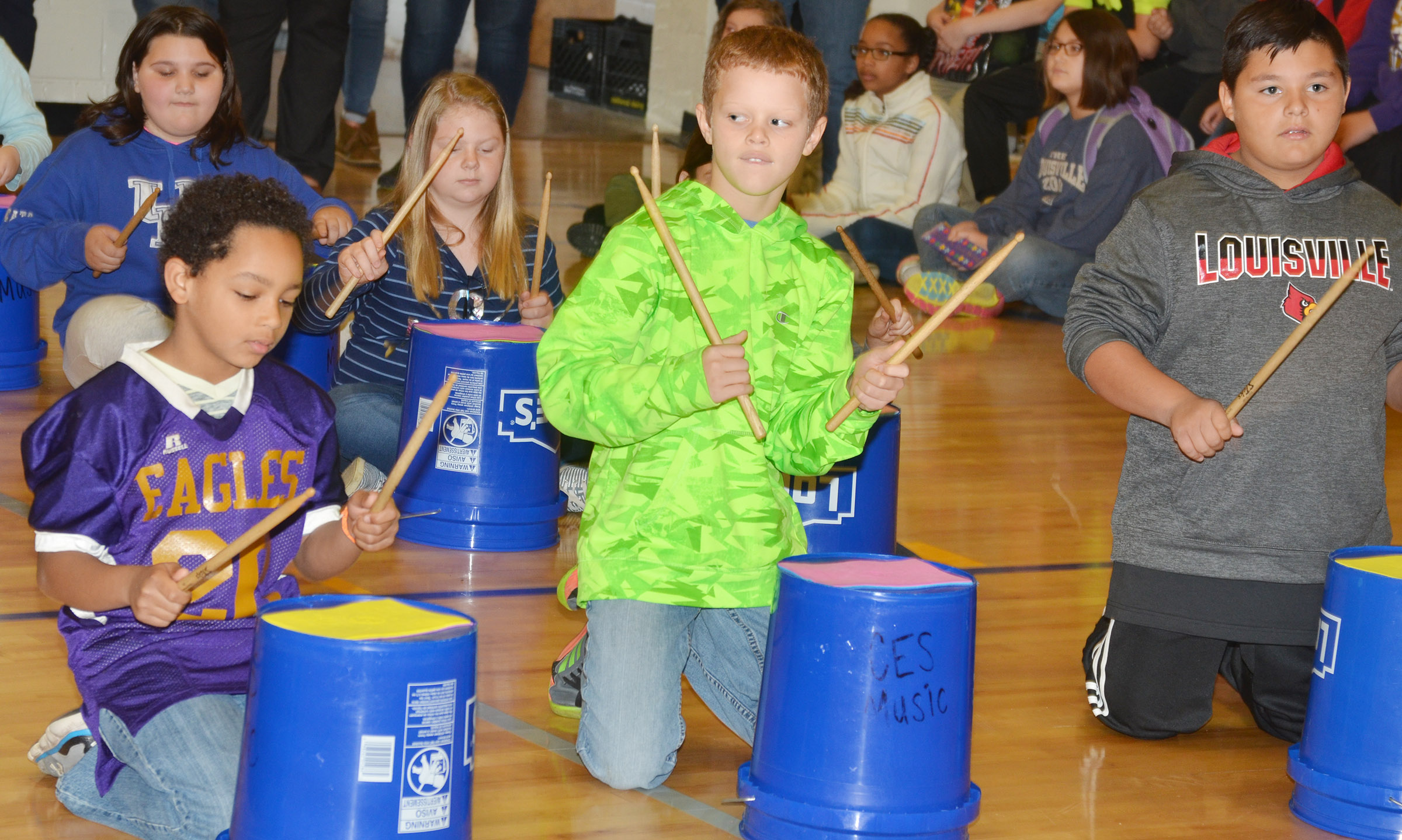 From left, CES fourth-graders Jalen Embry, Demetrious Dickens and Brayden Paiz play the bucket drums.