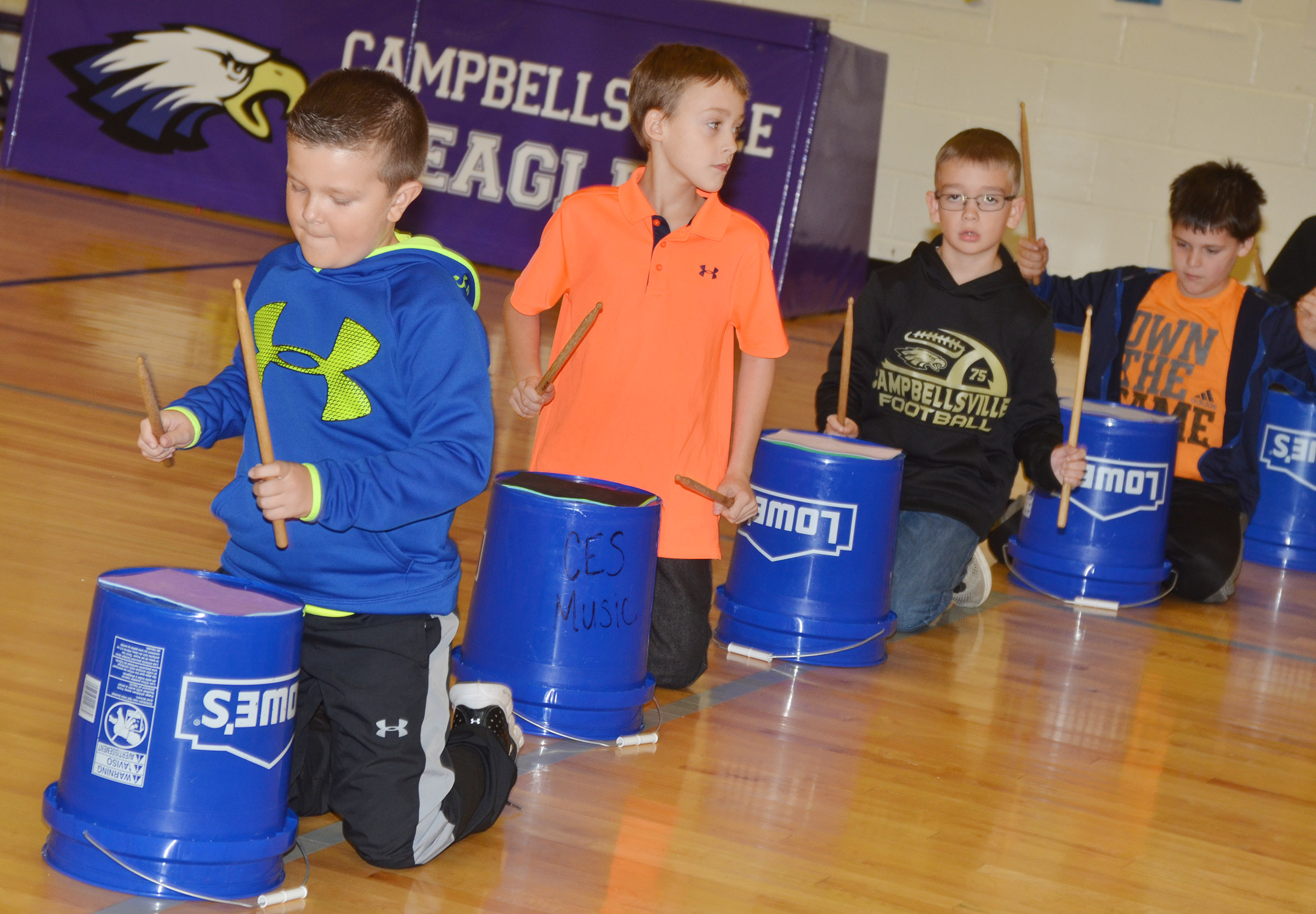 CES third-grader Cayton Lawhorn, at left, and, from left, fourth-graders Caysen Tungate, Cameron Estes and Chris Brown play the bucket drums.