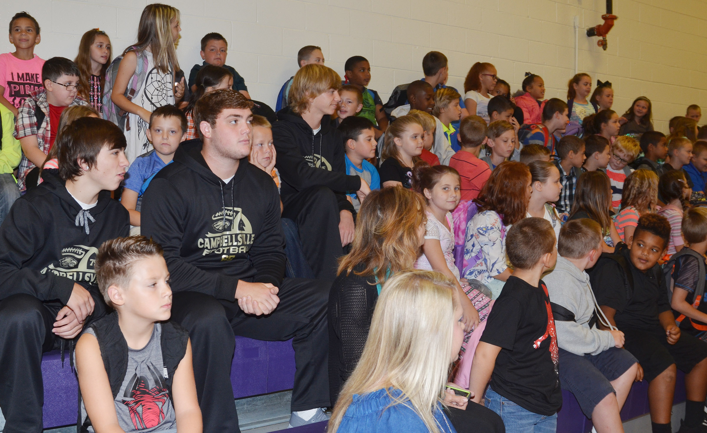 CHS football players, from left, senior Austin Carter, junior Lane Bottoms and freshman Arren Hash sit with CES students.
