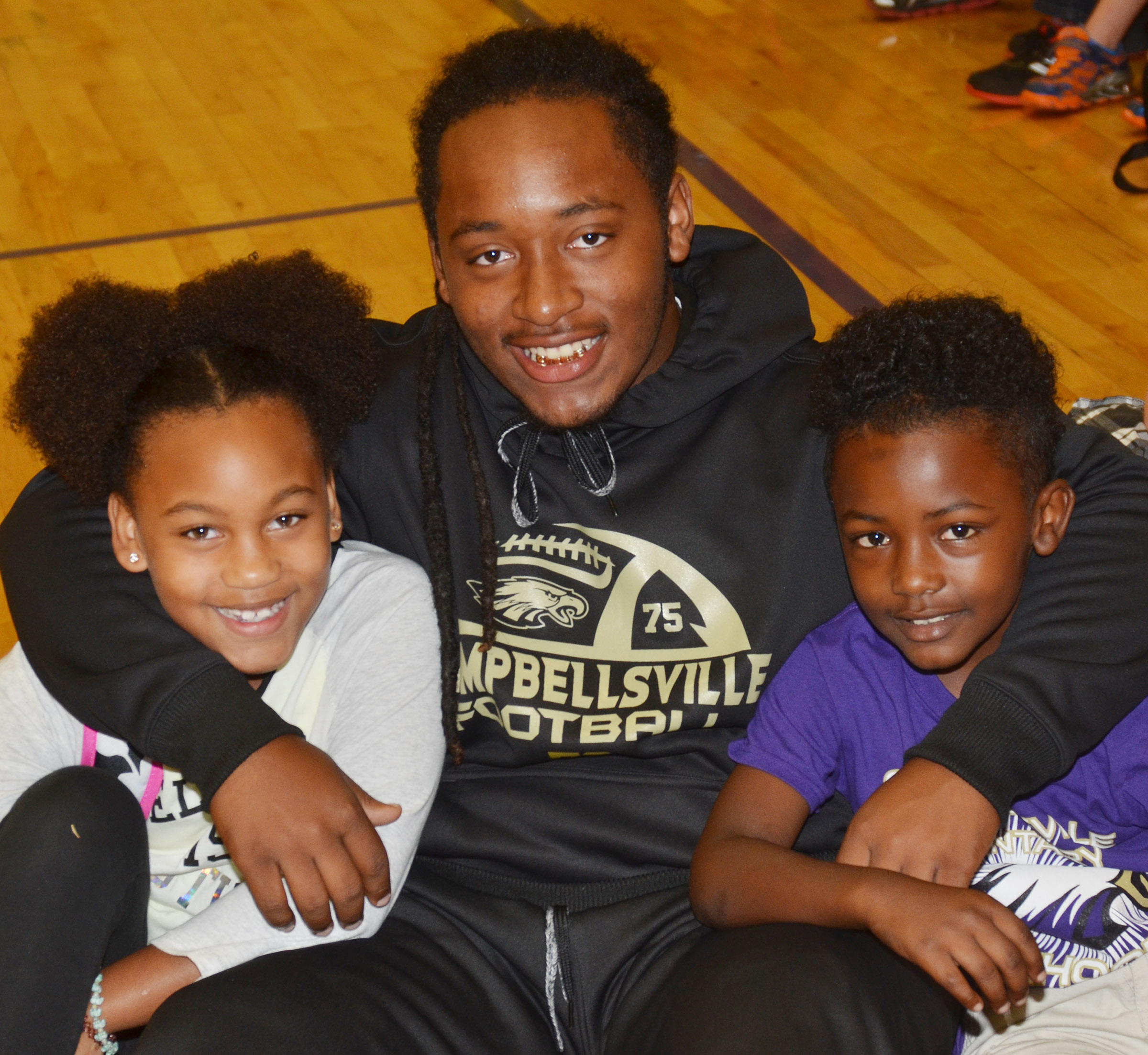CHS junior Ceondre Barnett smiles for a photo with CES second-graders Aliy Dunn, at left, and Drelynn Hollins.