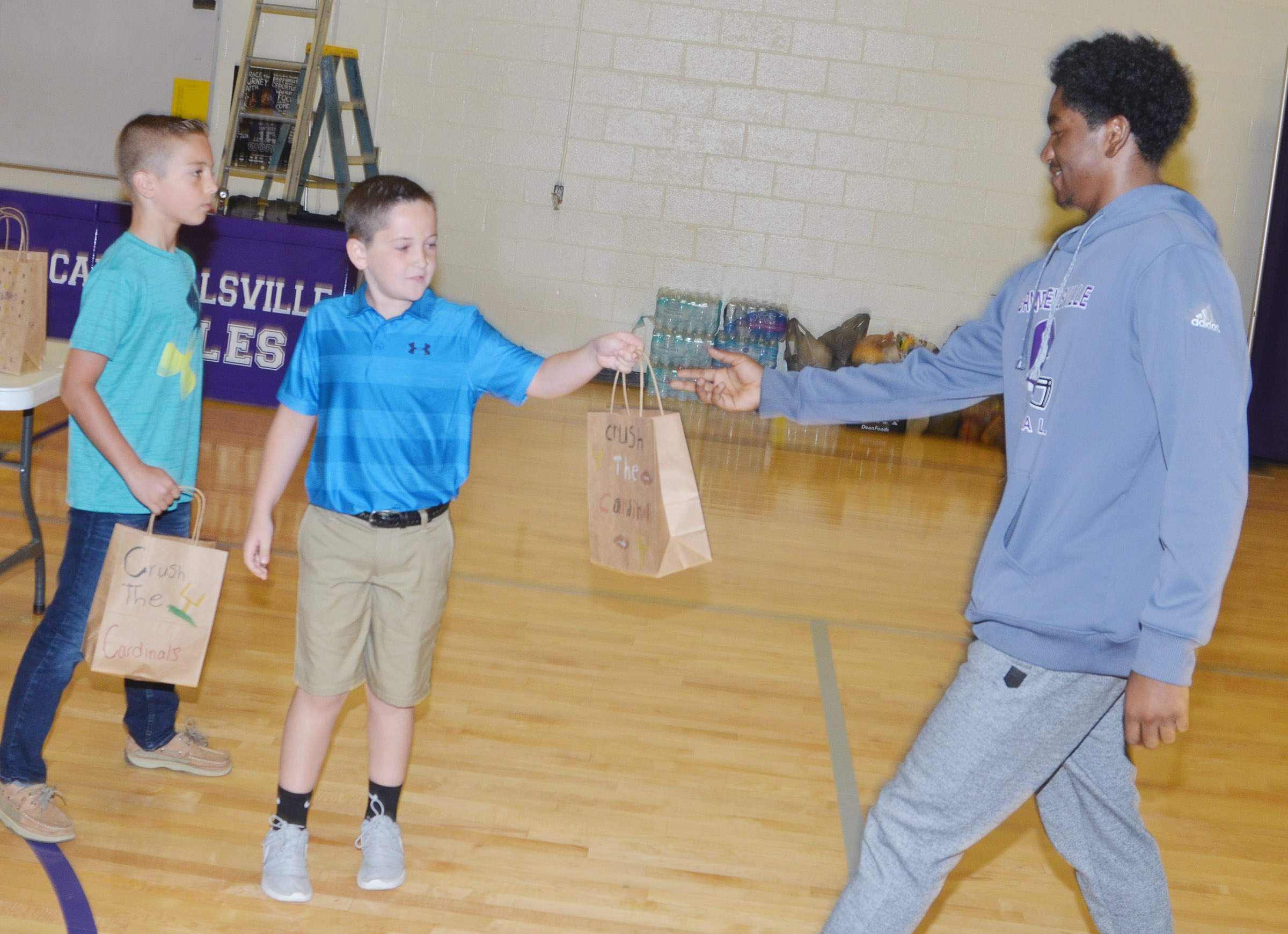 CHS senior Tyrion Taylor receives a treat bag from CES third-grader Luke Adkins.