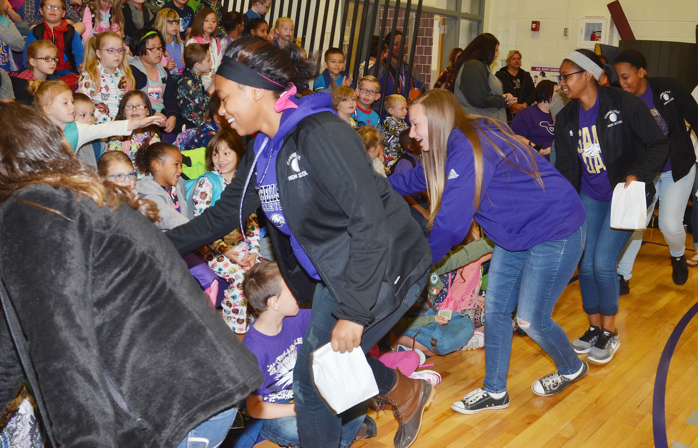 CHS volleyball players high-five CES students at their assembly on Friday, Oct. 13.