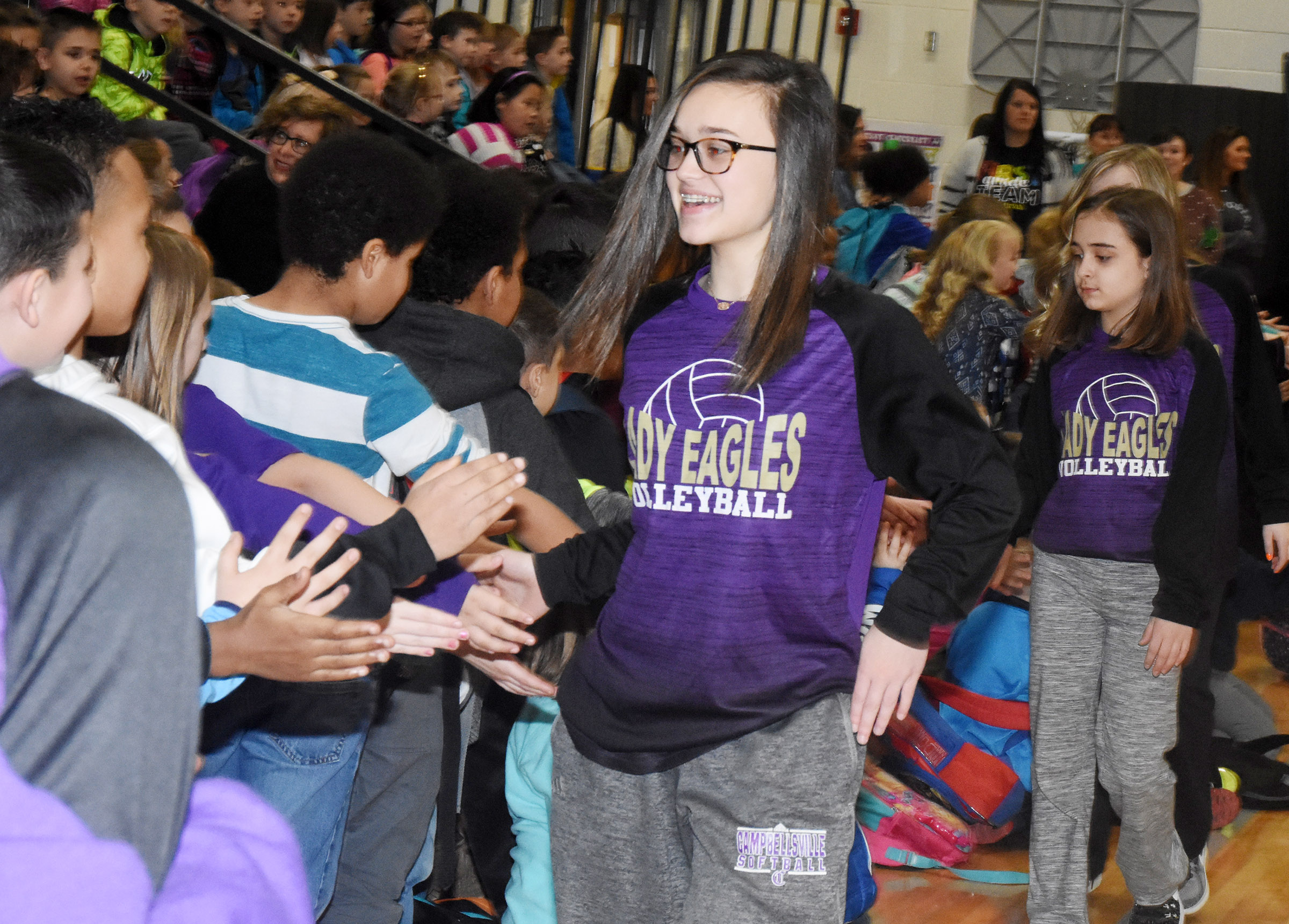 CMS eighth-grader and volleyball player Tayler Thompson gives high-fives.