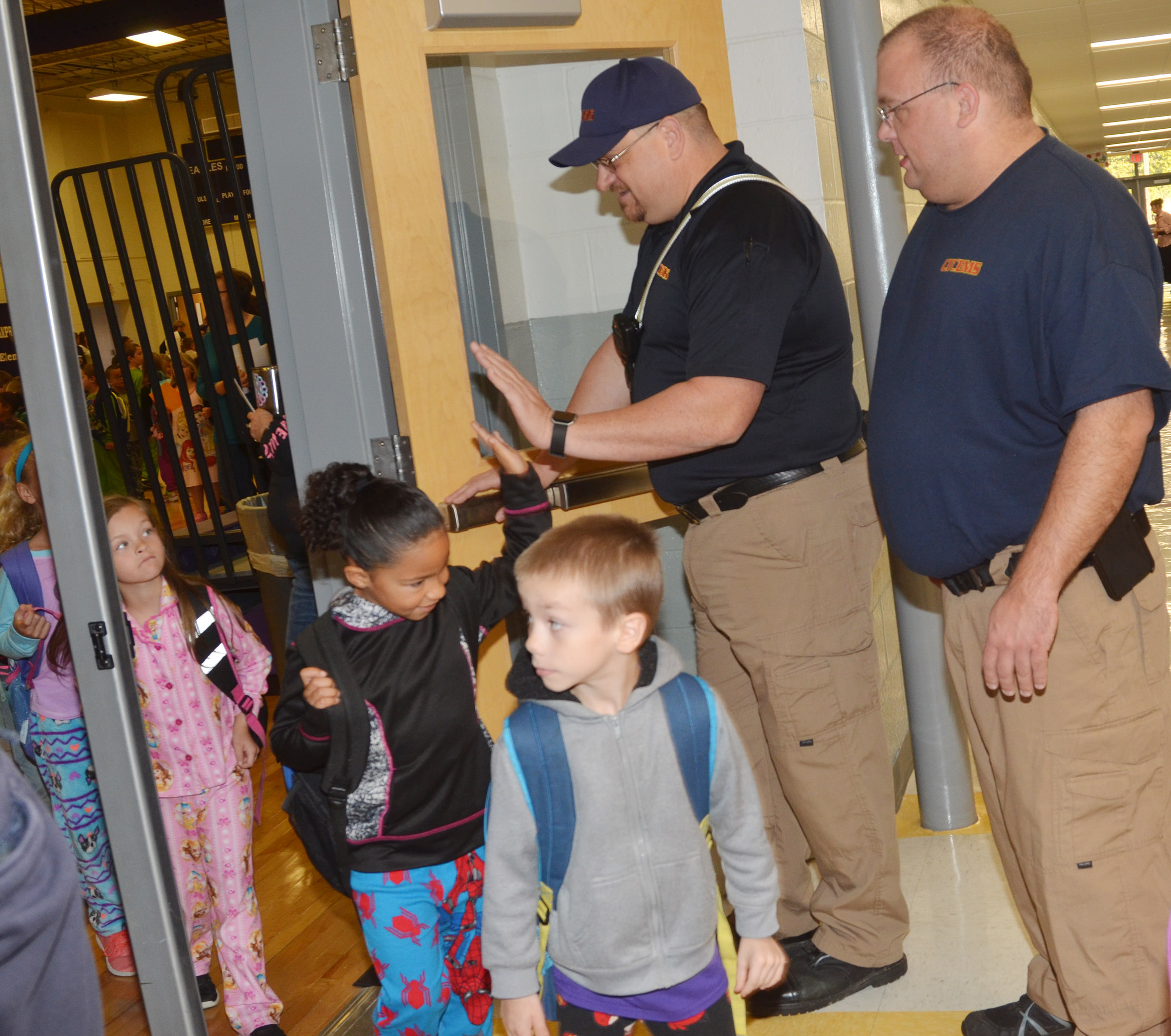Campbellsville/Taylor County EMS personnel Steve Marrs, at left, and Adam England greet and high-five CES students.