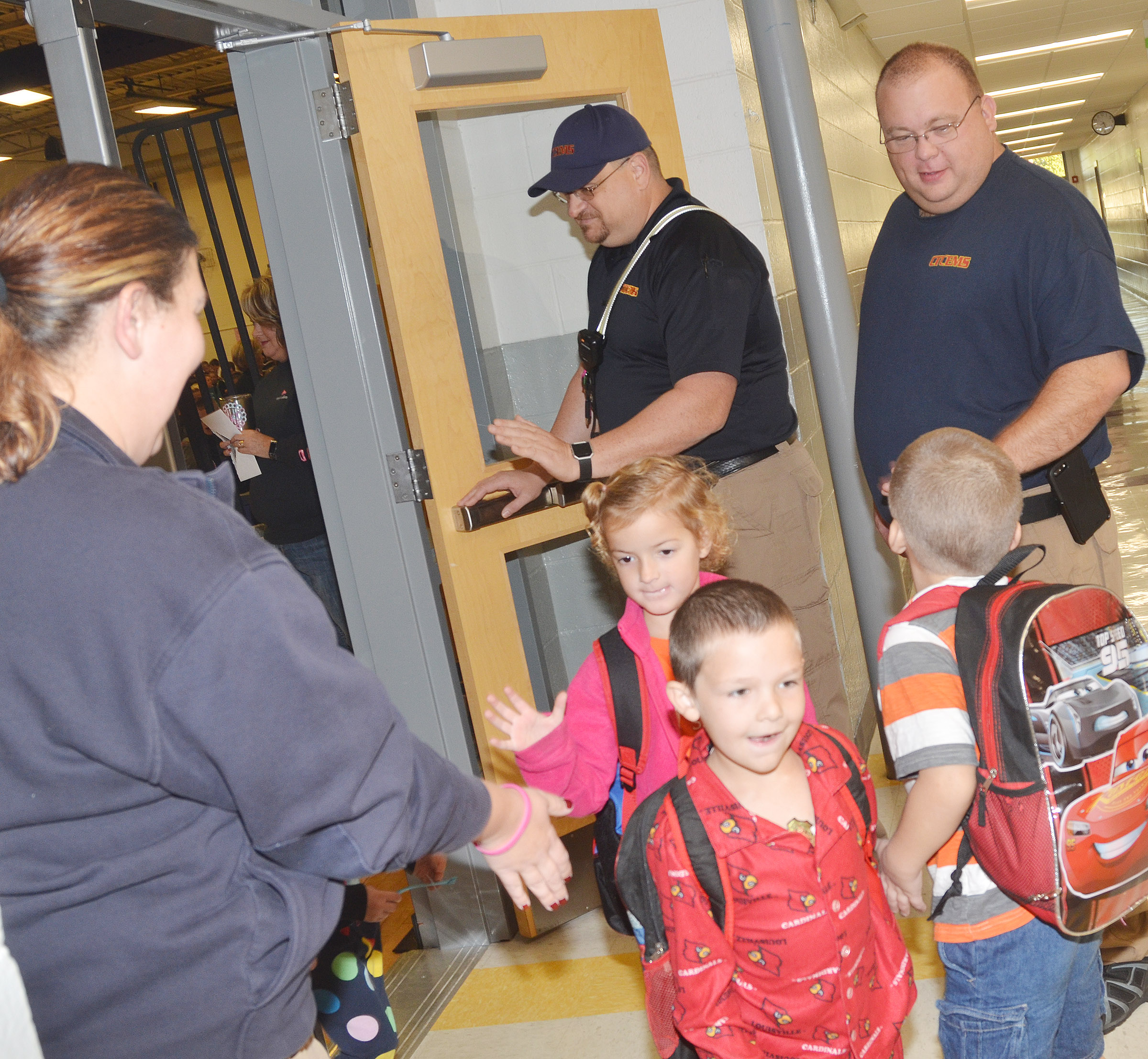 Campbellsville/Taylor County EMS personnel, from left, Jackie Fair, Steve Marrs and Adam England greet and high-five CES students.