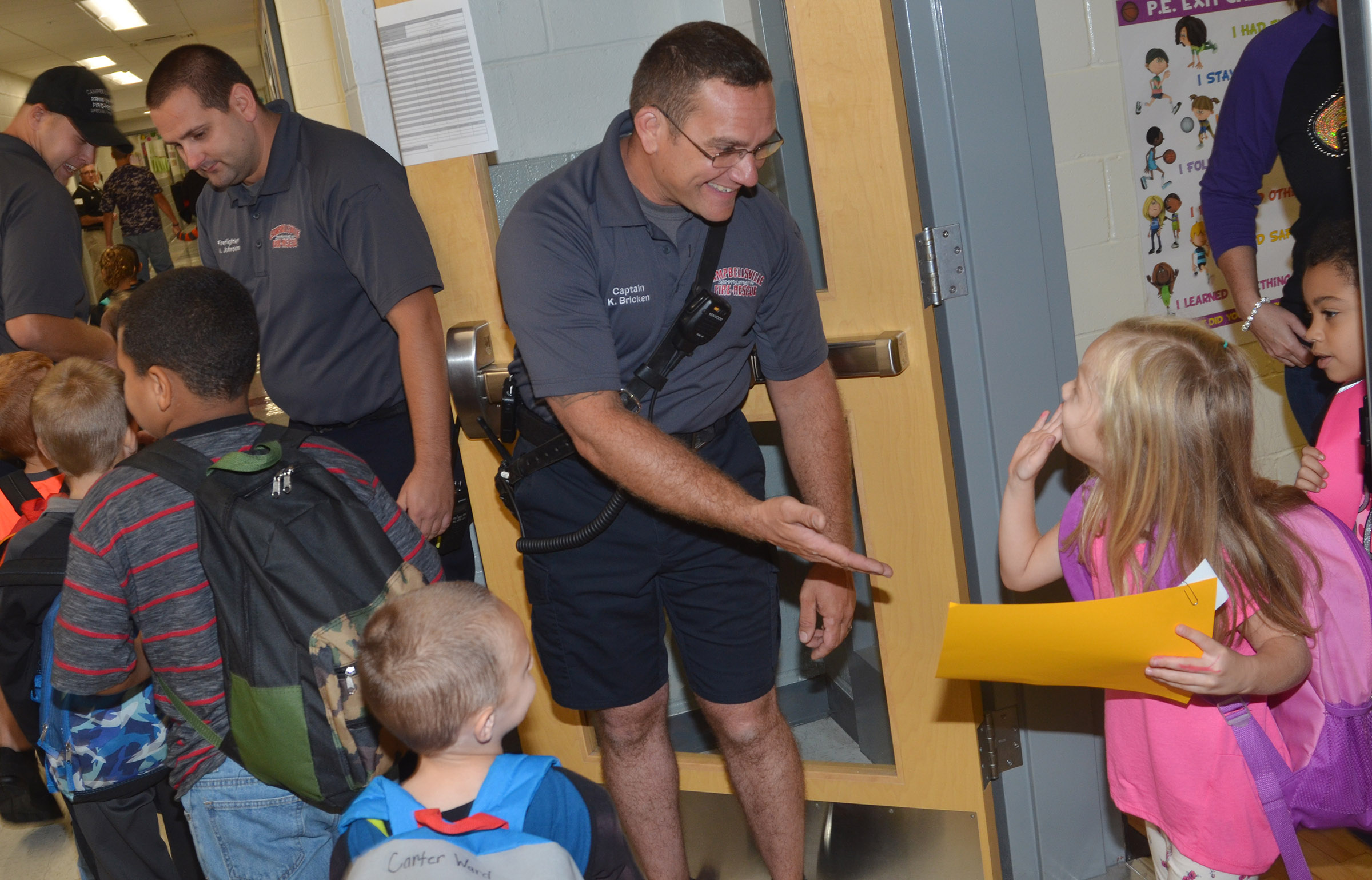 Campbellsville Fire & Rescue Captain Keith Bricken, center, and firefighters Daniel Lovett, at left, and Alex Johnson greet CES students.