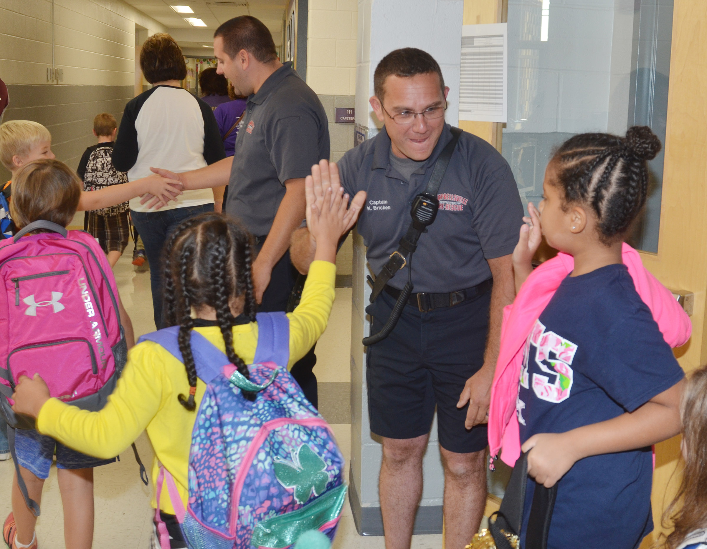 Campbellsville Fire & Rescue Captain Keith Bricken high fives CES students.