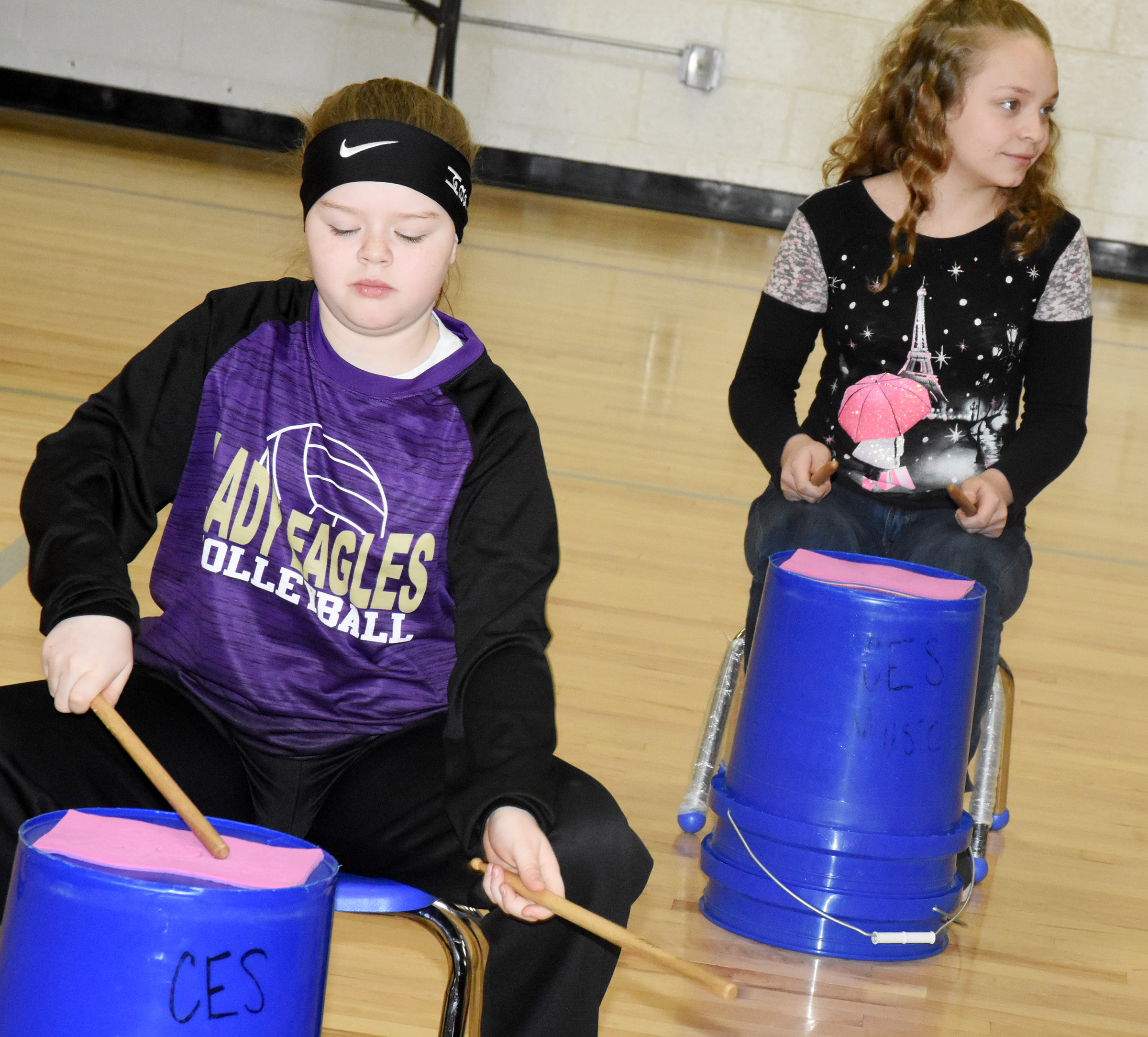 CES fifth-graders Miley Hash, at left, and Deanna Reardon play the bucket drums.
