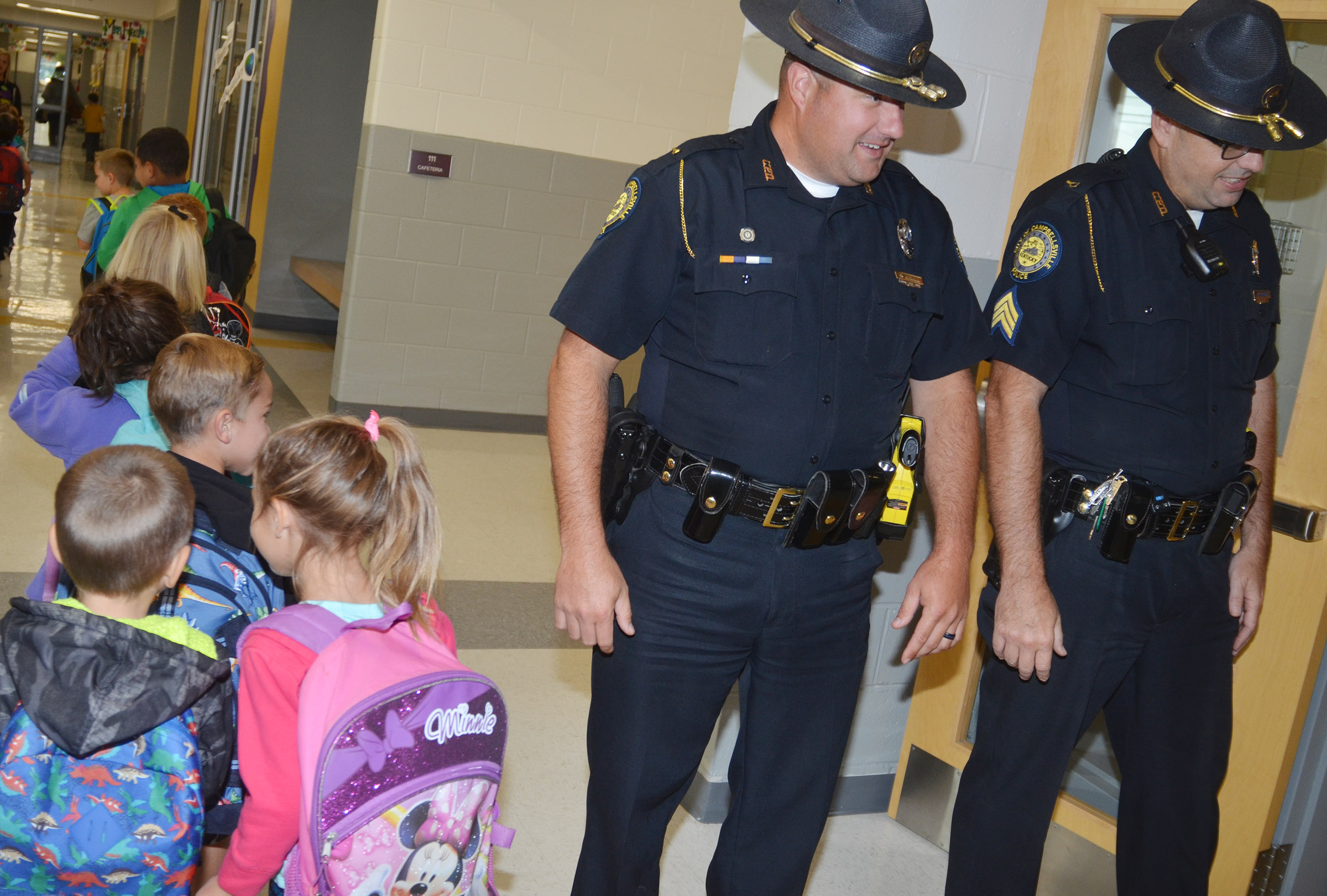 Campbellsville Police officers Ryan Jewell, at left, and David Tucker greet CES students as they walk to their classrooms.