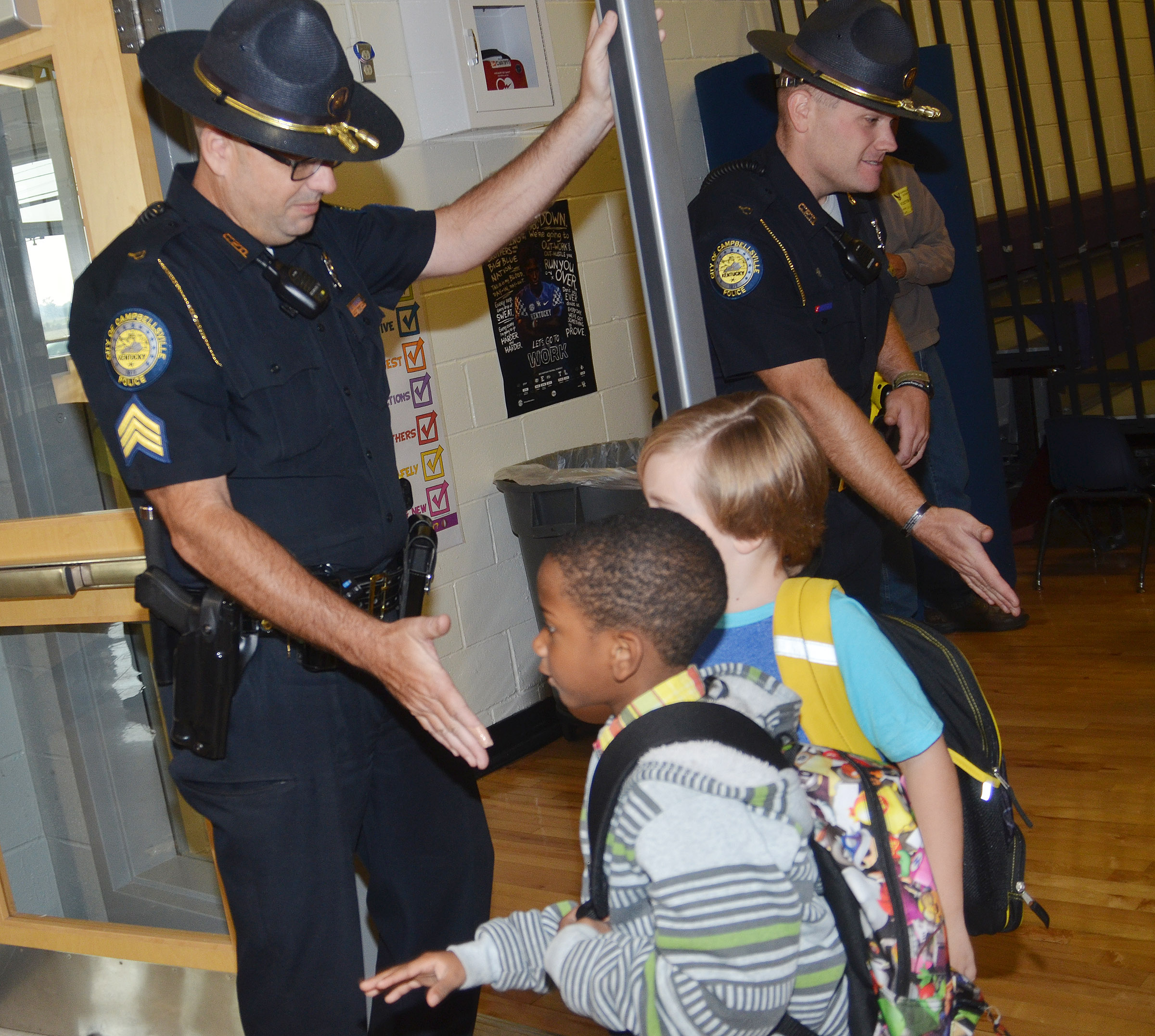 Campbellsville Police officers David Tucker, at left, and Jake Hedgespeth greet CES students as they walk to their classrooms.