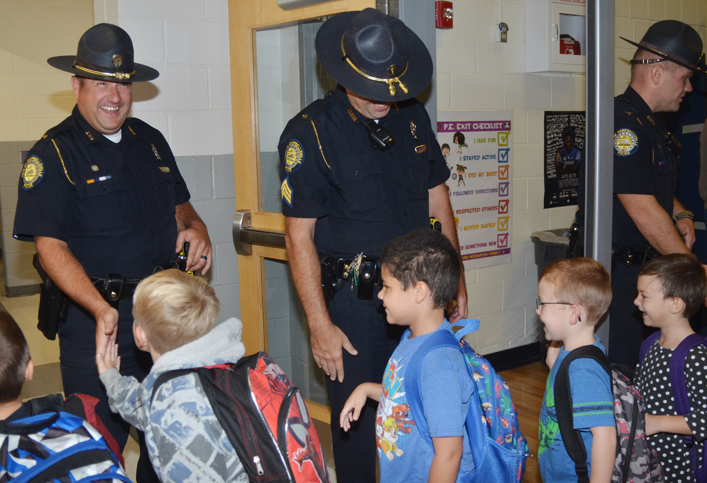 From left, Campbellsville Police officers Ryan Jewell, David Tucker and Jake Hedgespeth greet CES students as they walk to their classrooms.