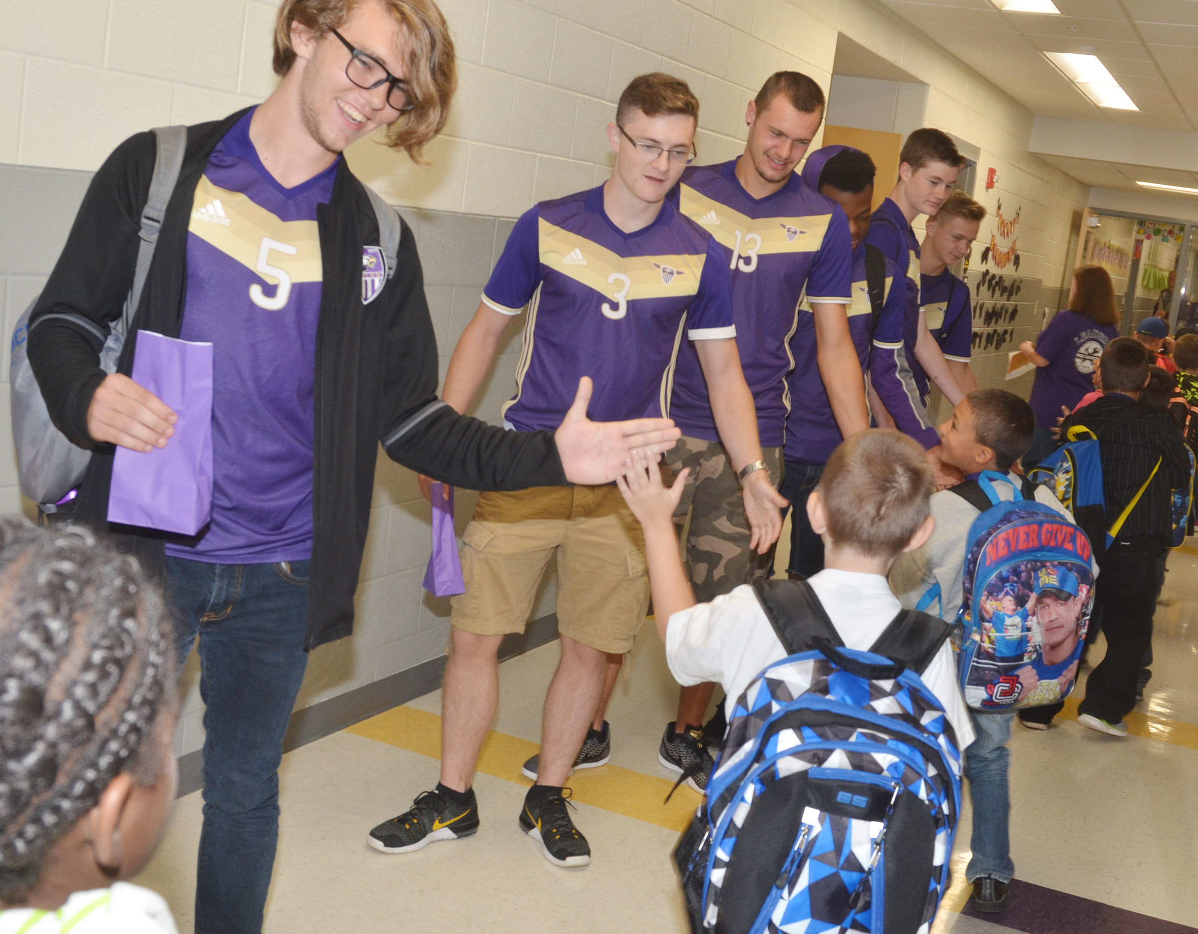 From left, CHS seniors Christian Berry, Bryce Richardson and Logan Cole and their teammates high five CES students.