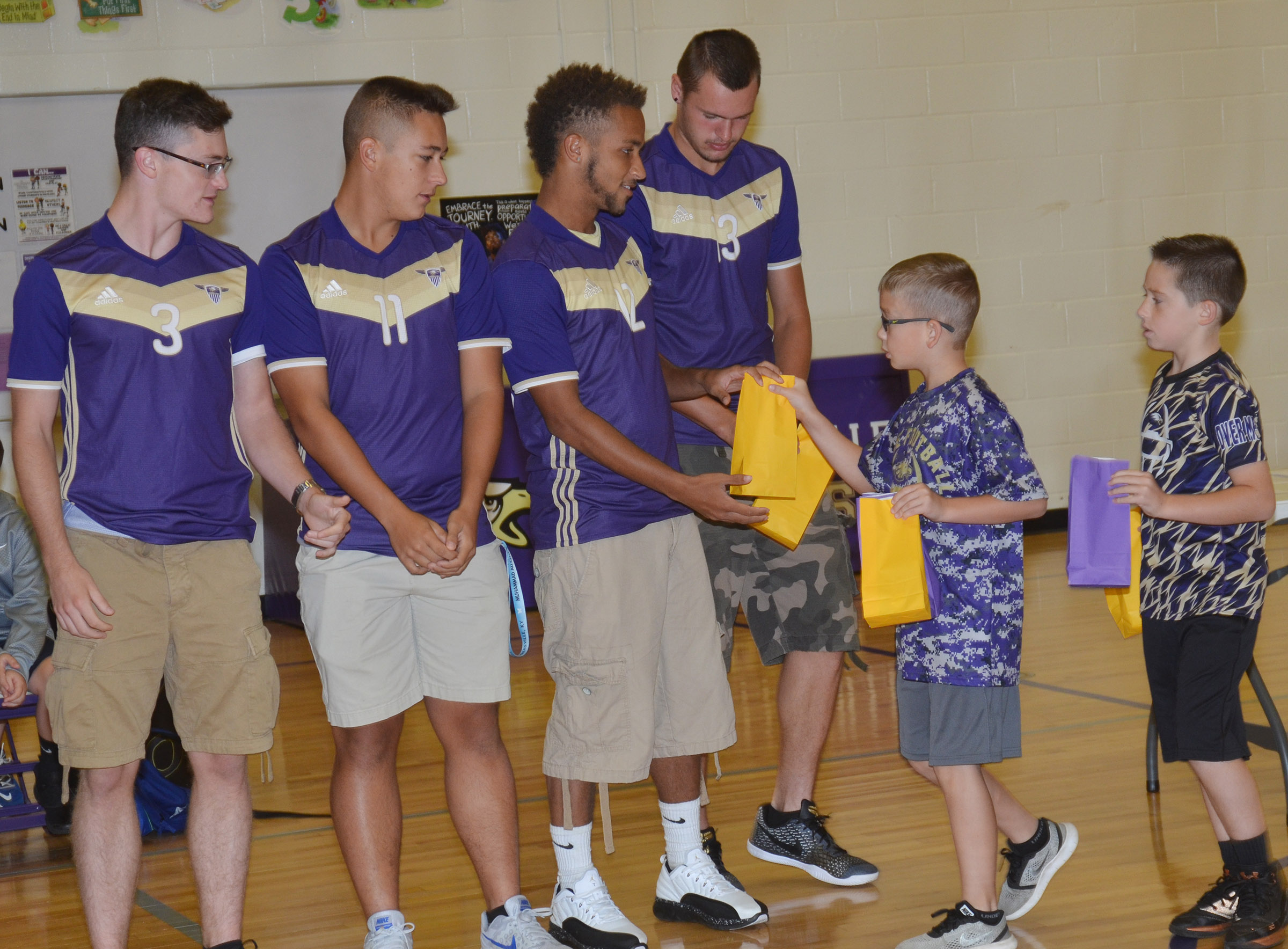 CES fourth-grader Cameron Estes, at left, and third-grader Lanigan Price give CHS soccer players, from left, seniors Bryce Richardson, Cody Davis, Ethan Lay and Logan Cole.