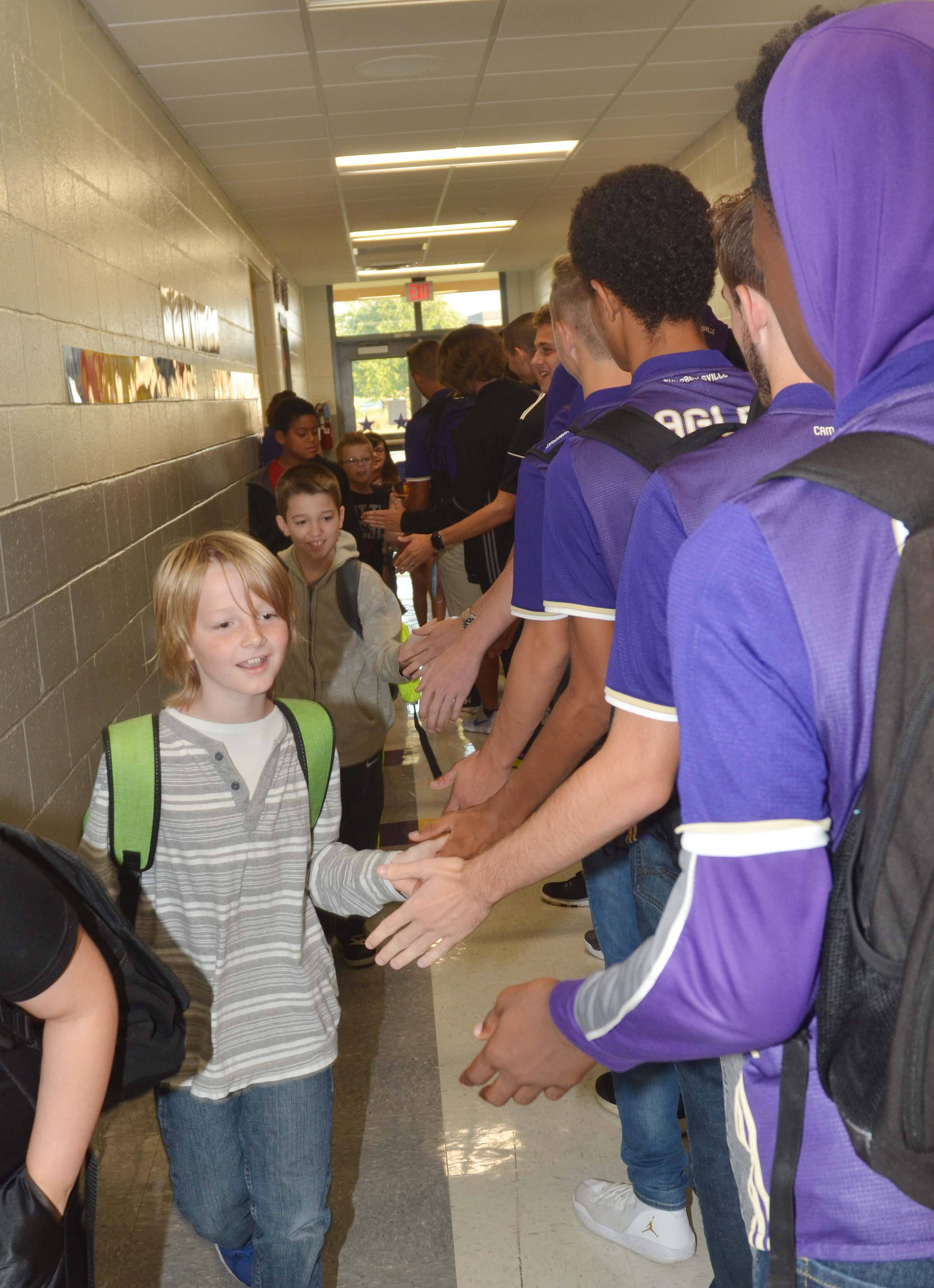 CES fourth-grader Devin Underwood high fives CHS soccer players.