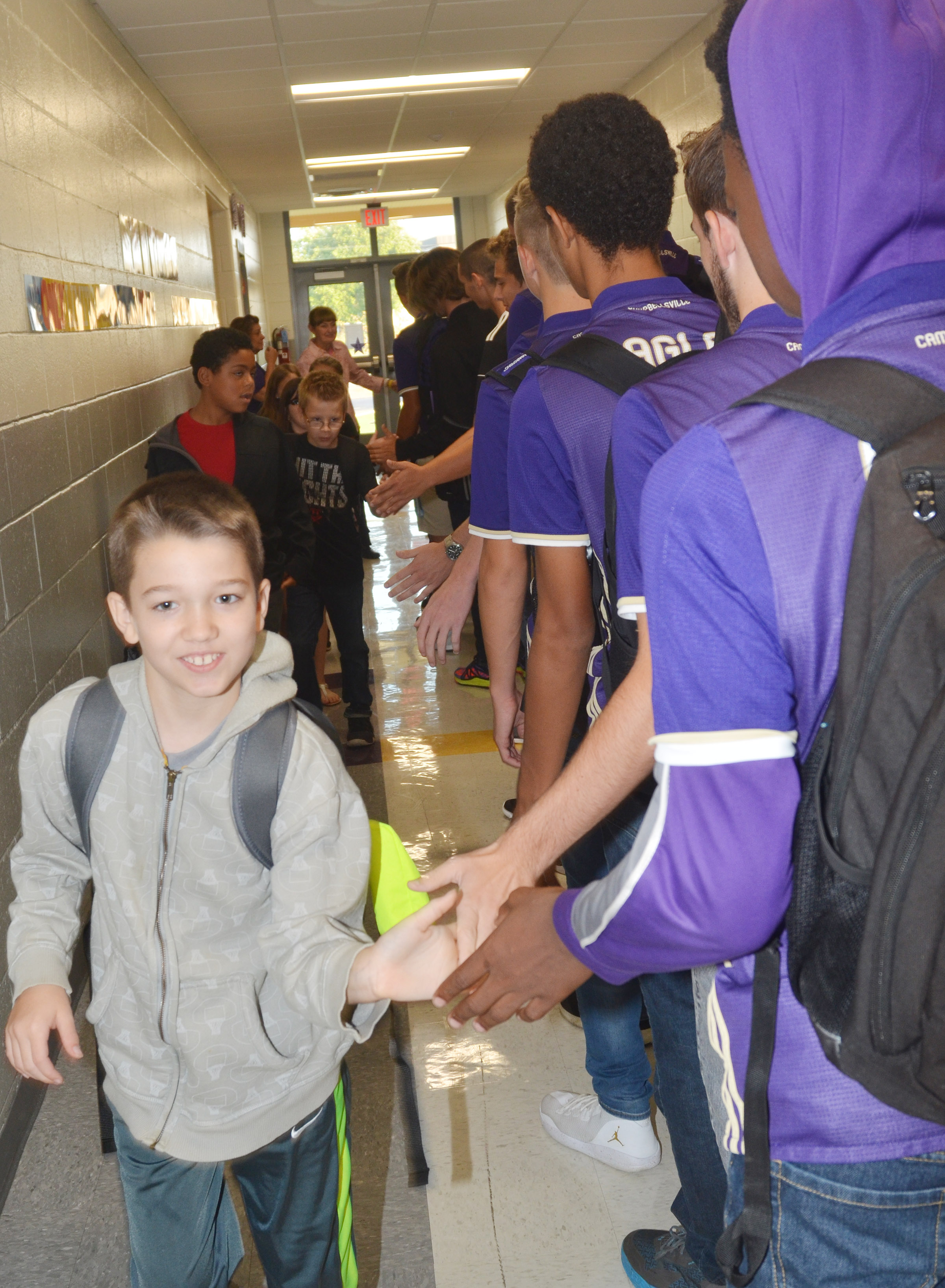 CES fourth-grader Landon Tucker high fives CHS soccer players.