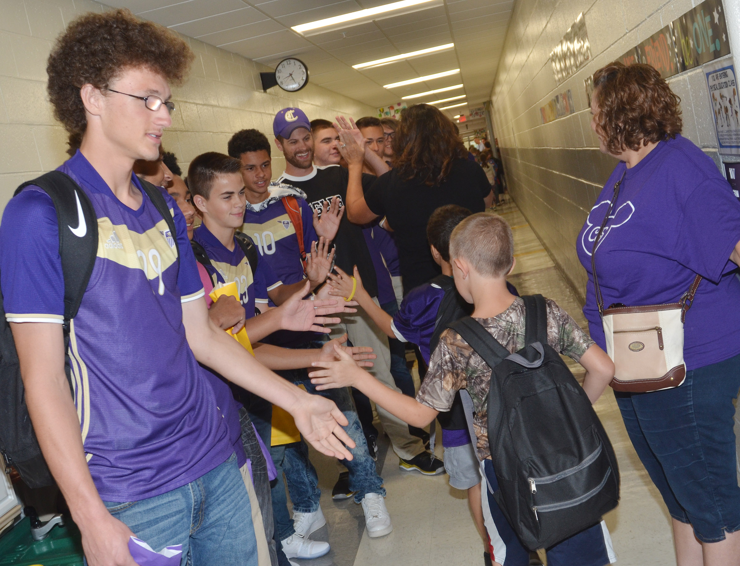 CHS sophomore Brennon Wheeler and his teammates high five CES students.
