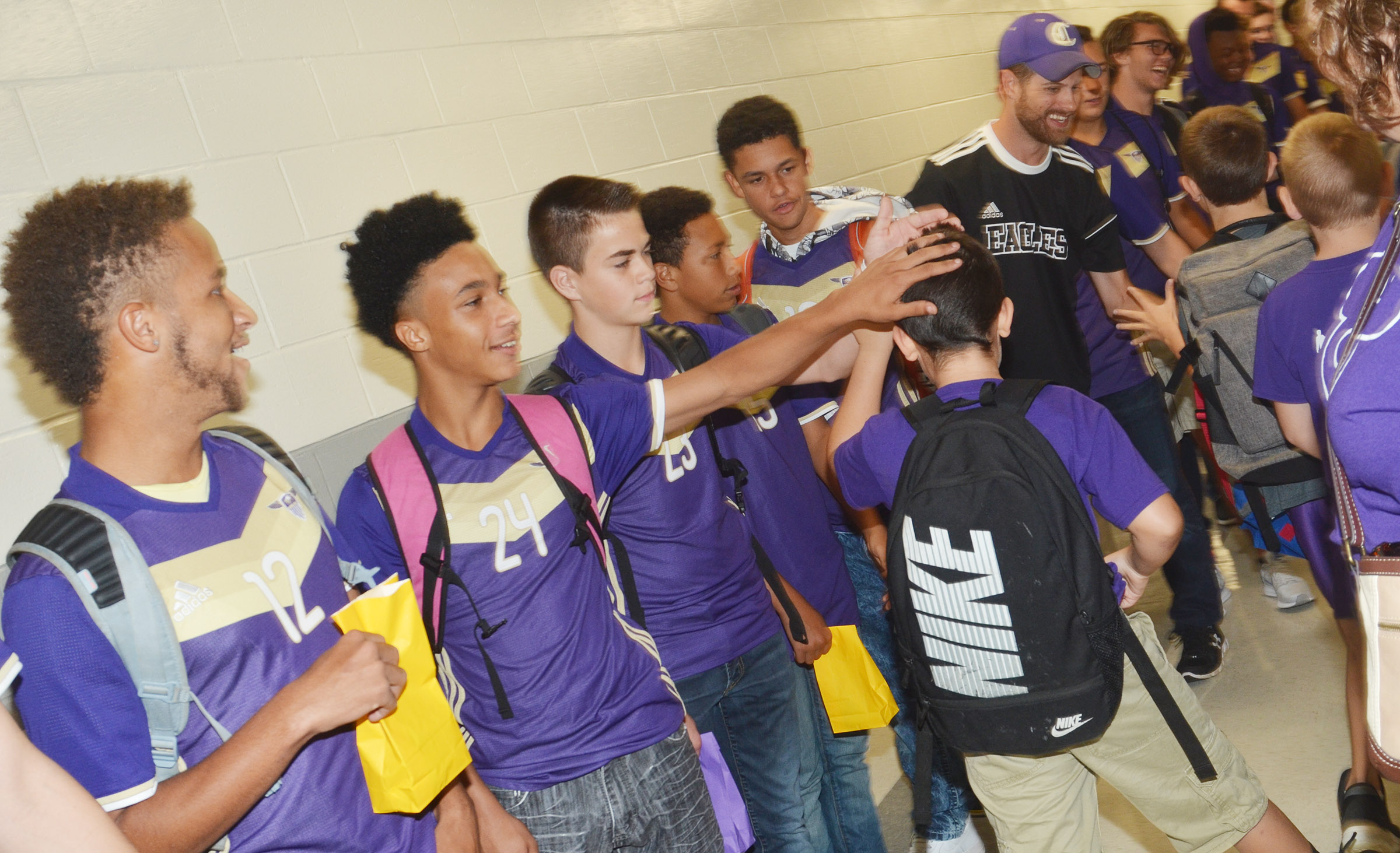 From left, CHS soccer players Ethan Lay, a senior, junior Daniel Johnson, freshmen Clark Kidwell and Jastyn Shively, sophomore Mikael Vaught and assistant coach Matthew Schmuck greet CES students.