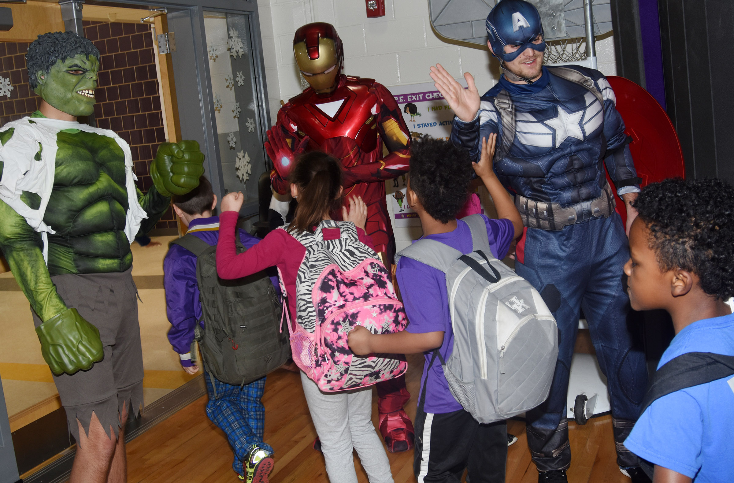 From left, Hulk, Iron Man and Captain America give high-fives.