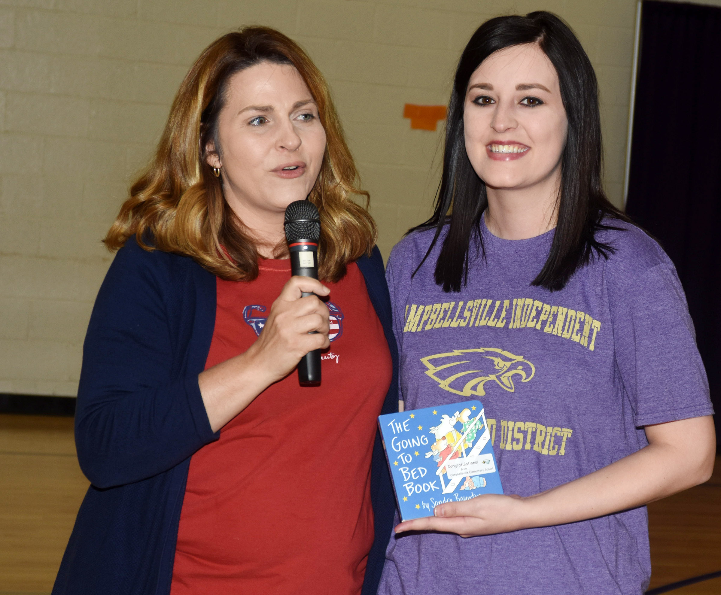 "CES Guidance Counselor Sonya Orberson, at left, presents fourth-grade teacher Samantha Coomer with a copy of ""The Going to Bed Book"" by Sandra Boynton. Parents who deliver their babies at Taylor Regional Hospital will receive a copy of the book, compliments of CES. Coomer gave birth to her son about two and a half months ago at TRH."