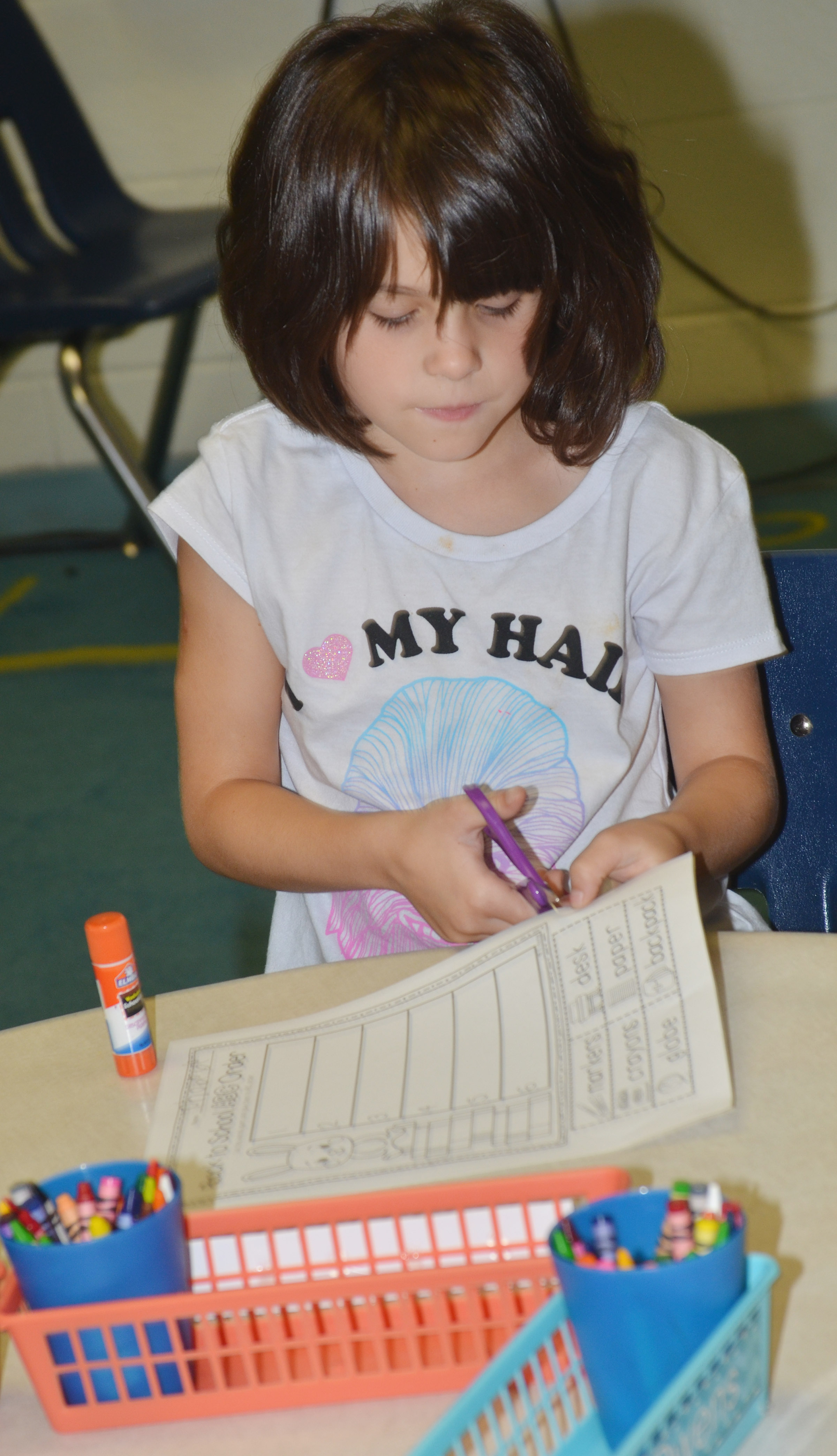 CES first-grader Phoebe Ritchie cuts out the words on her worksheet.