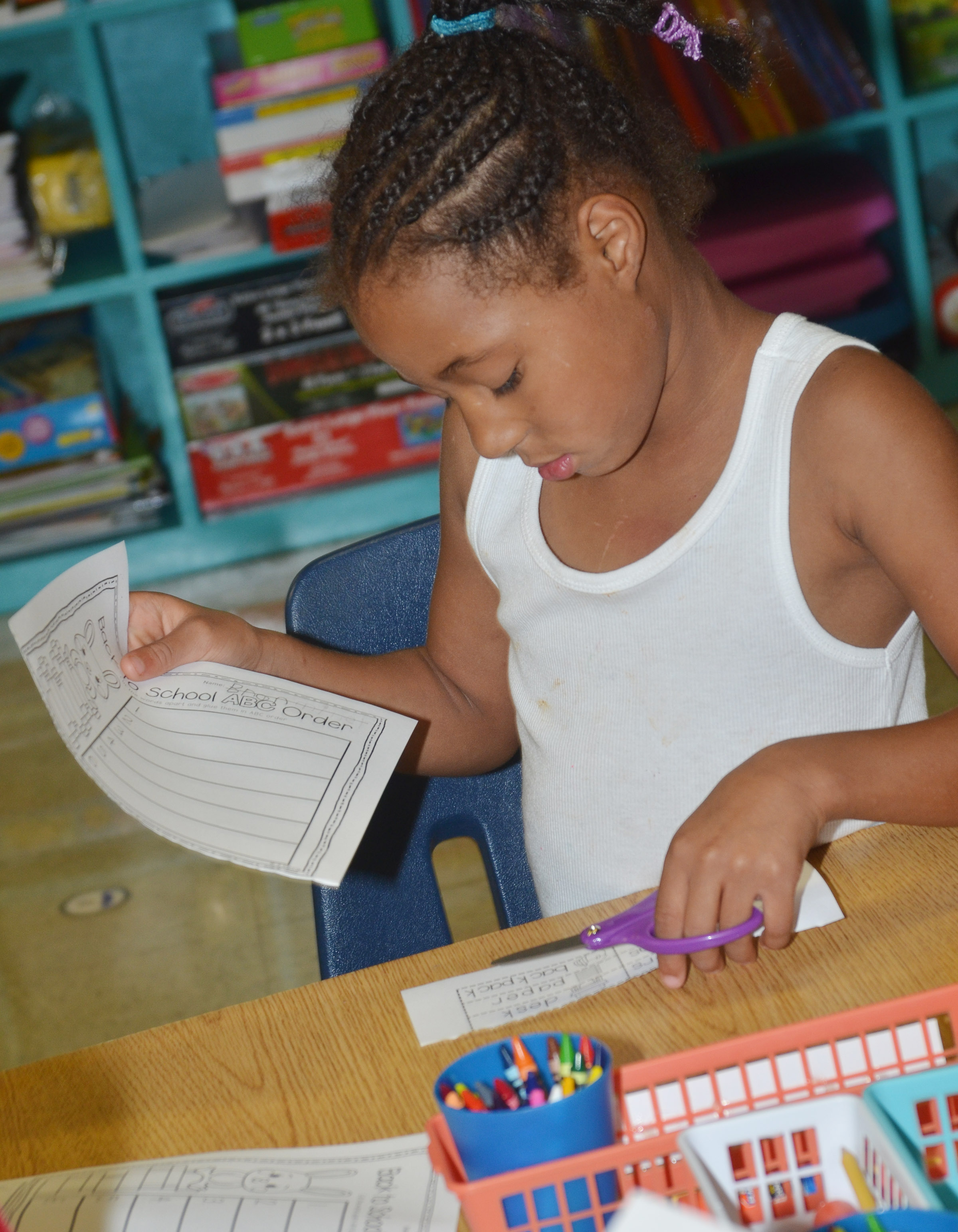 CES first-grader Brea Miller cuts out the words on her worksheet.