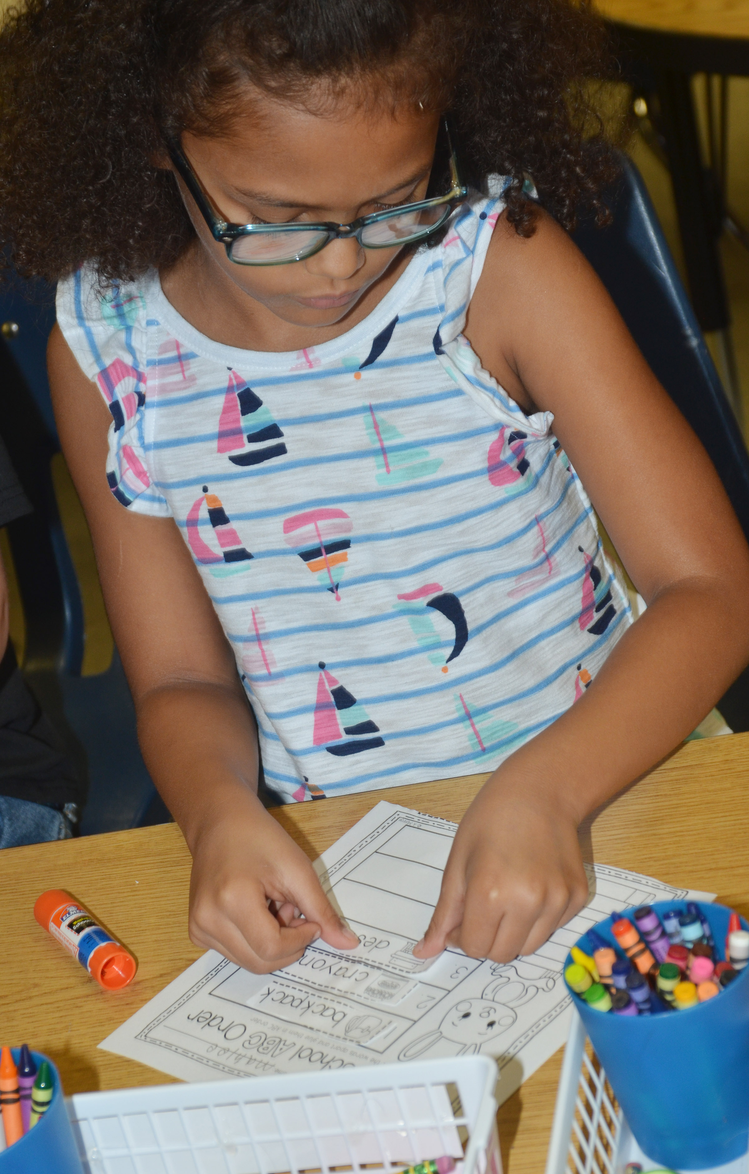 CES first-grader Marlee Dickens glues her words in alphabetical order.