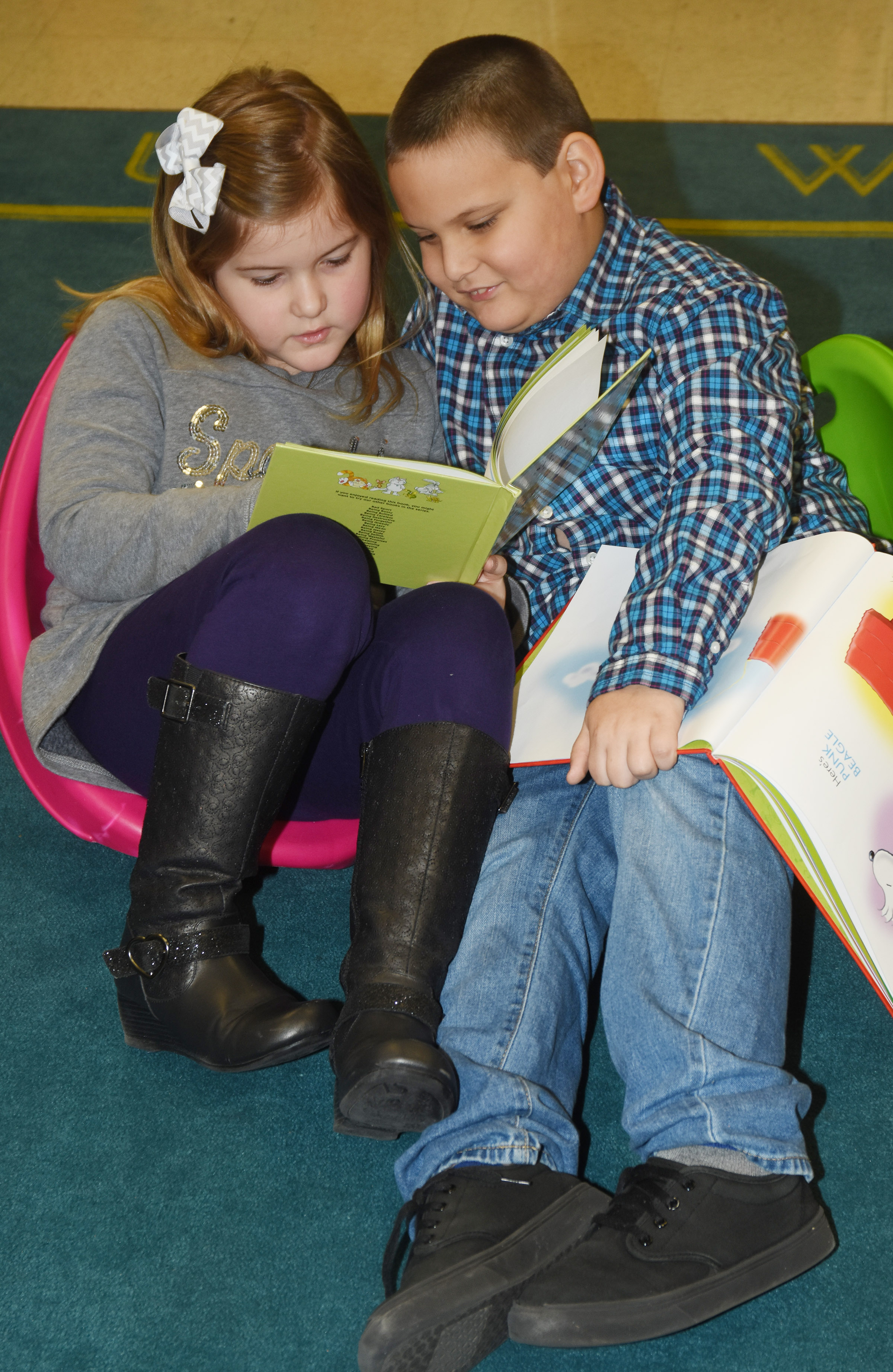 CES first-graders Aubreigh Knifley, at left, and Cloud Malone read together.