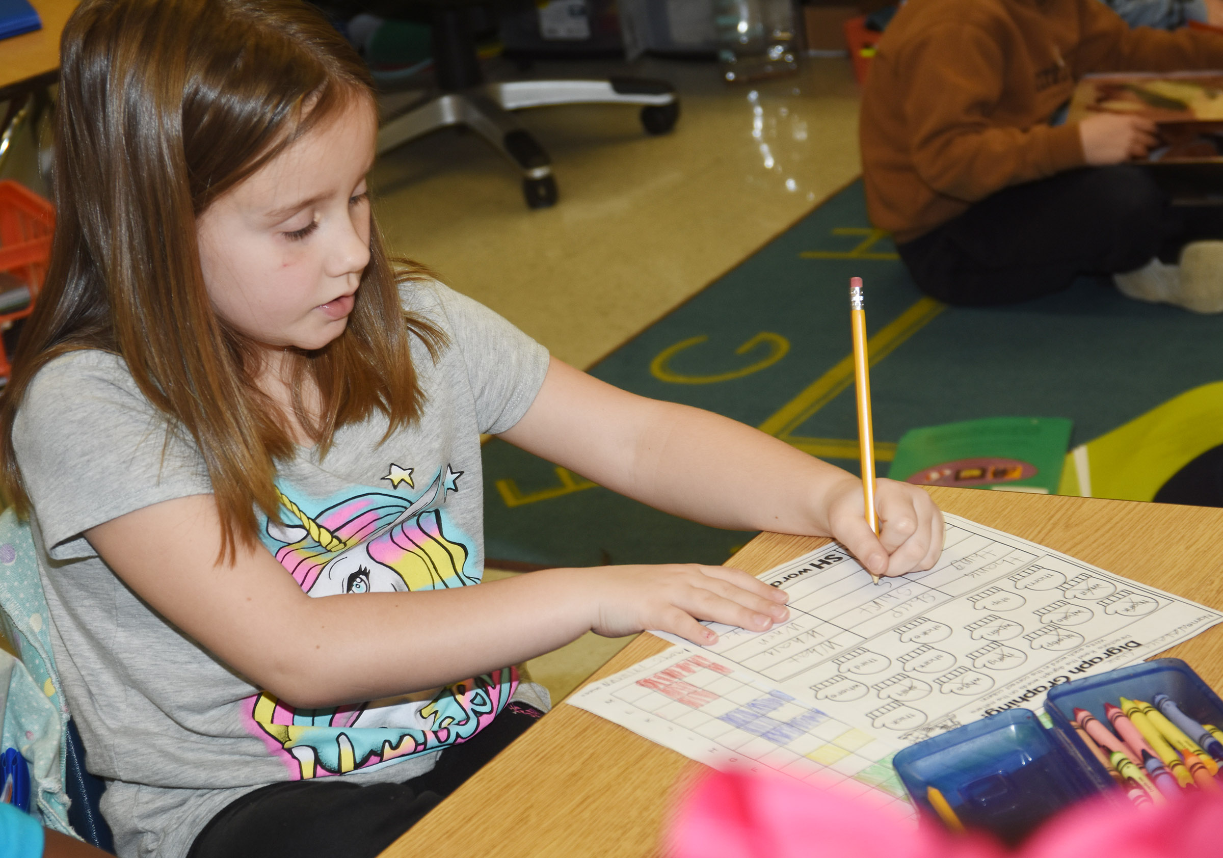 "CES first-grader Natalee Shaw writes words that begin with ""sh,"" ""th"" and ""wh."""