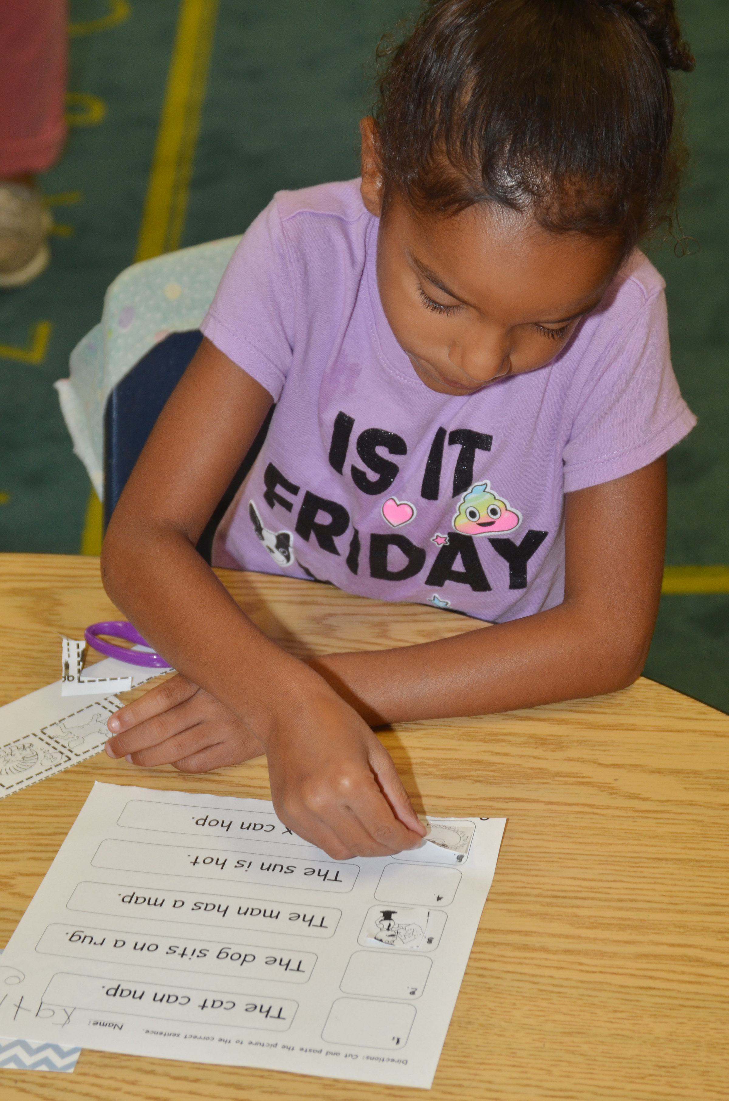 CES first-grader Kaylee Thompson glues the pictures on her worksheet.