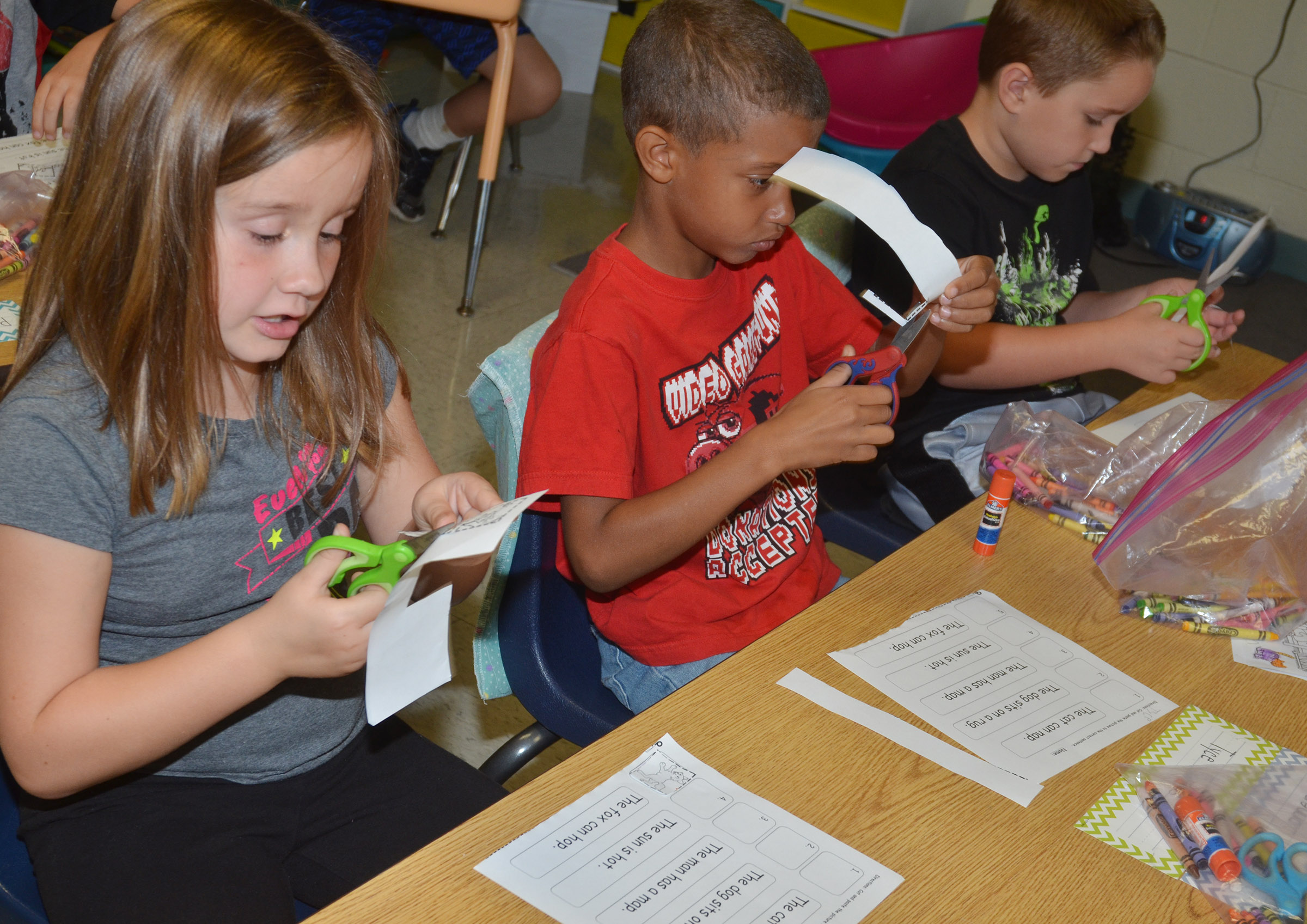 From left, CES first-graders Natalee Shaw, Tyce Owens and Kaiden Bradfield cut out the pictures on their worksheets.
