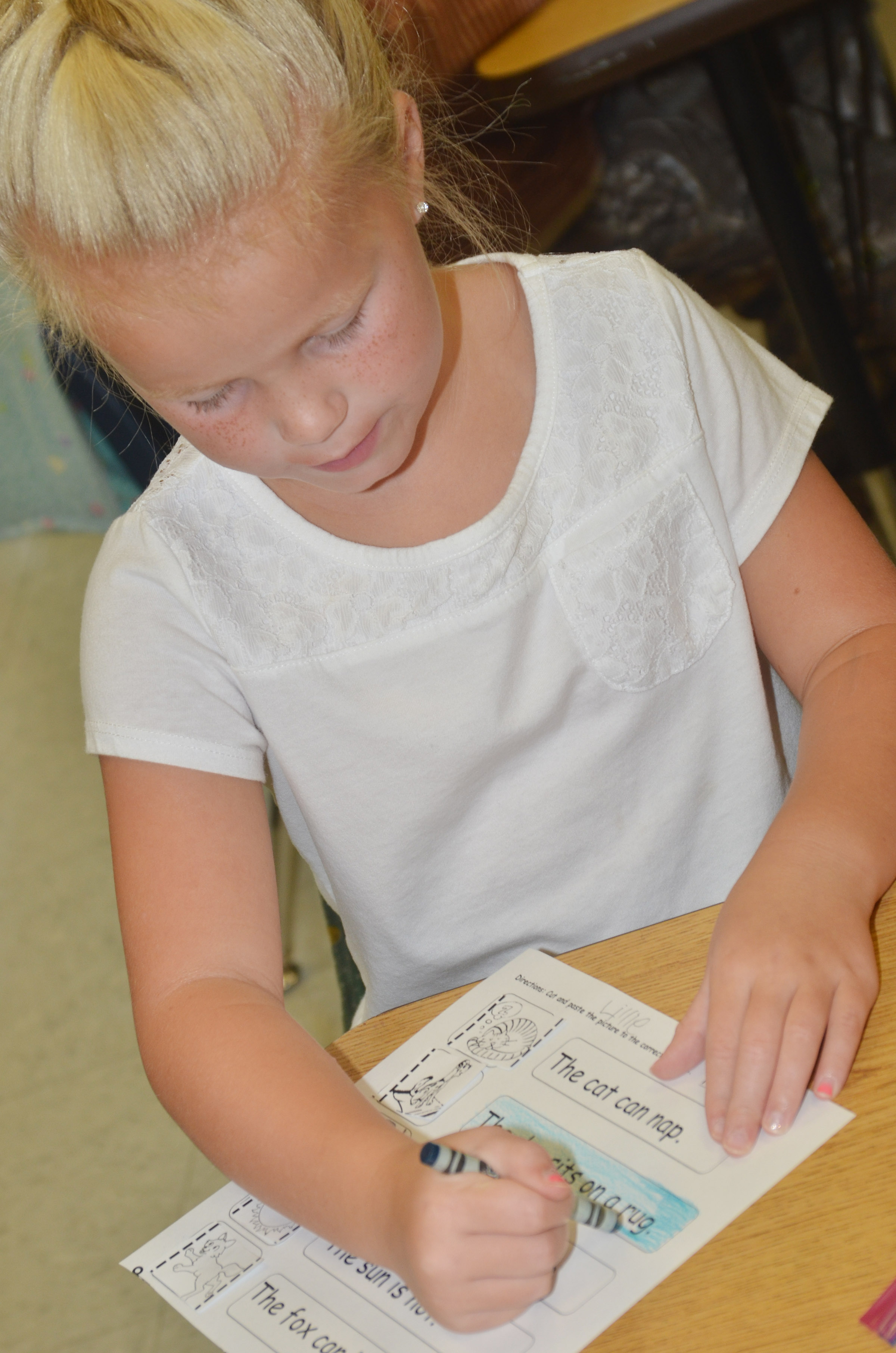 CES first-grader Lillie Judd colors her worksheet.