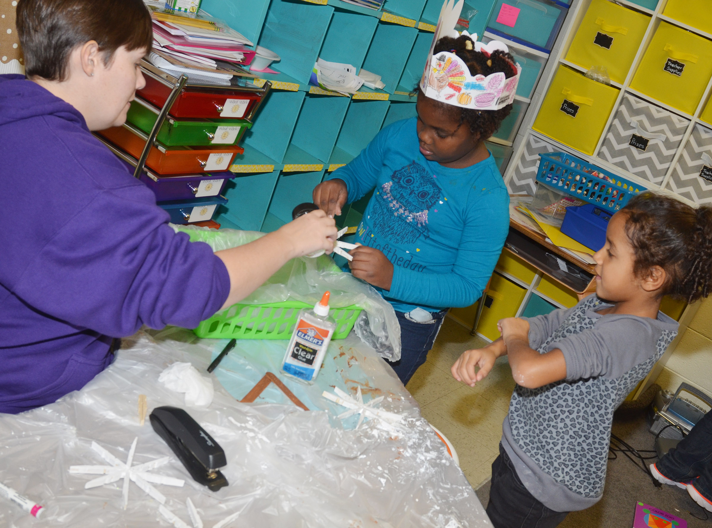 CES first-grader Destinee Henry-Turner adds glitter to her snowflake ornament, with some help from her teacher Amanda Barnett. First-grader Kylei Thompson, at right, waits her turn.