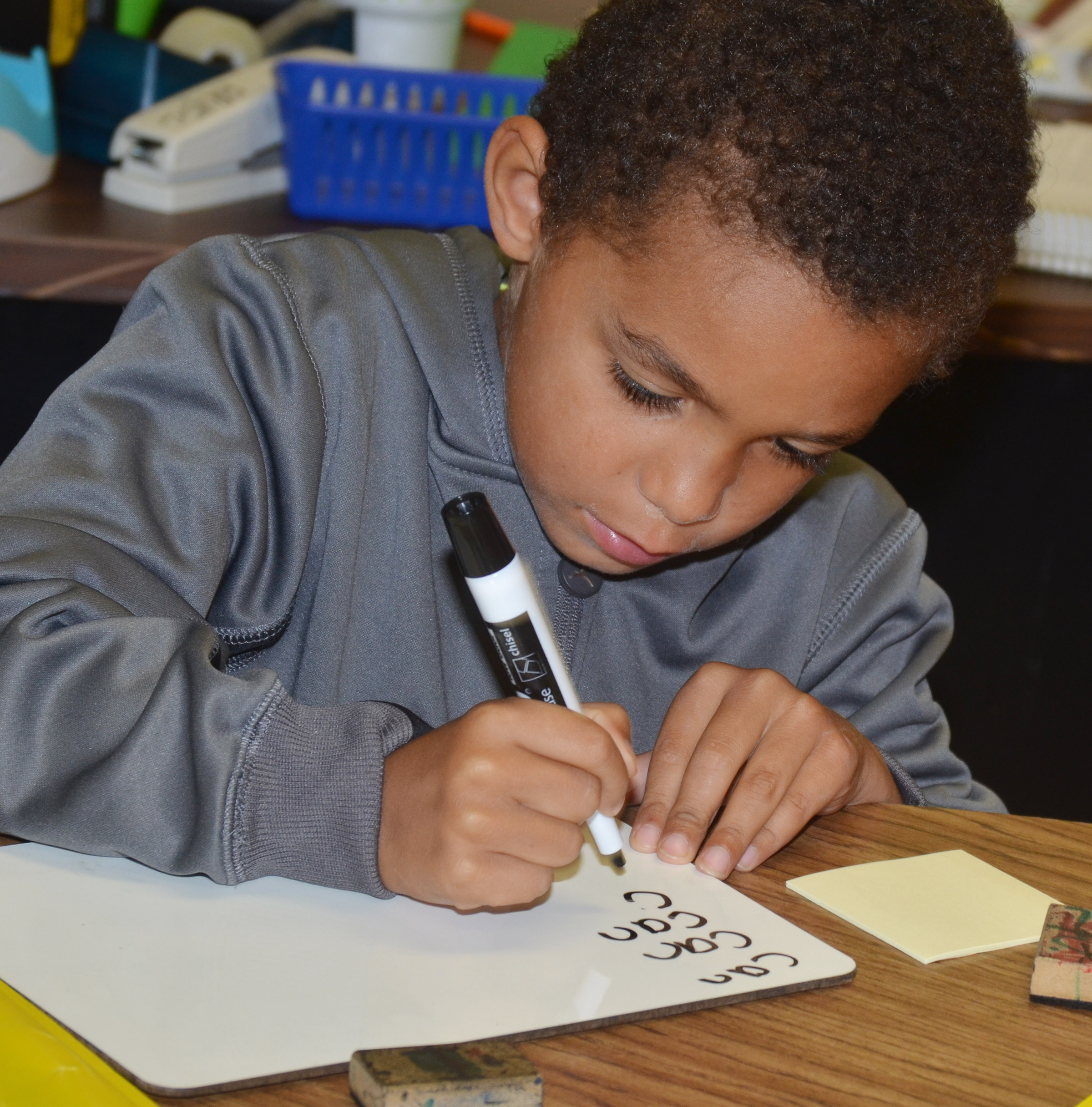 "CES first-grader Quincy Travis writes the word ""can."""