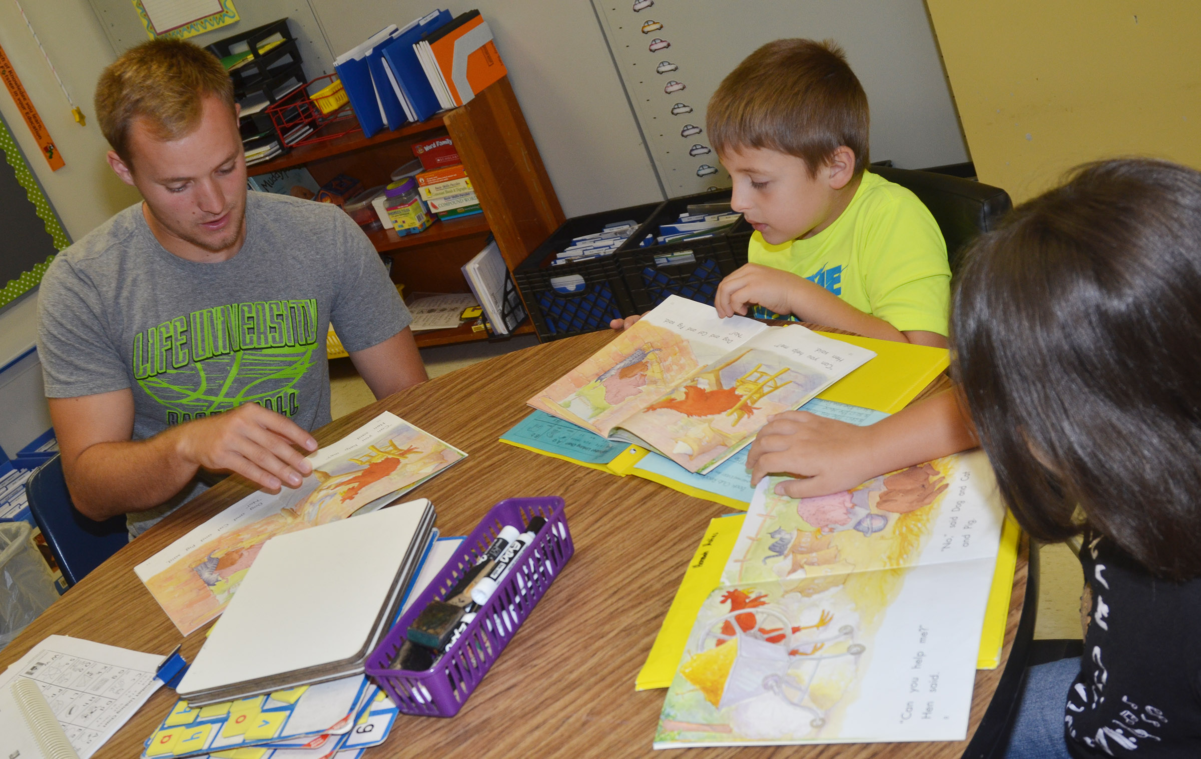CES AmeriCorps tutor Bradley Bates reads with first-graders Ayden Andrew and Hannah Matias.