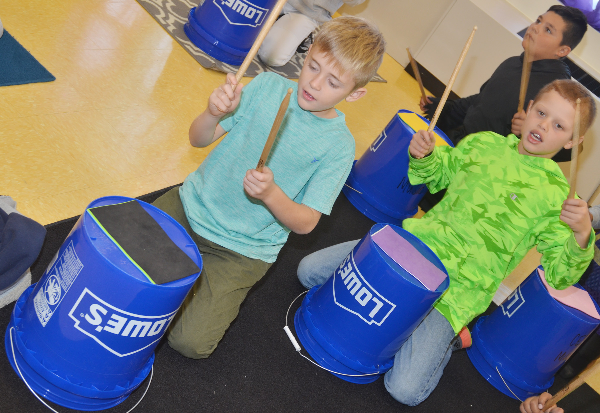 CES fourth-graders Braydn Spurling, at left, and Demetrious Dickens play the bucket drums.