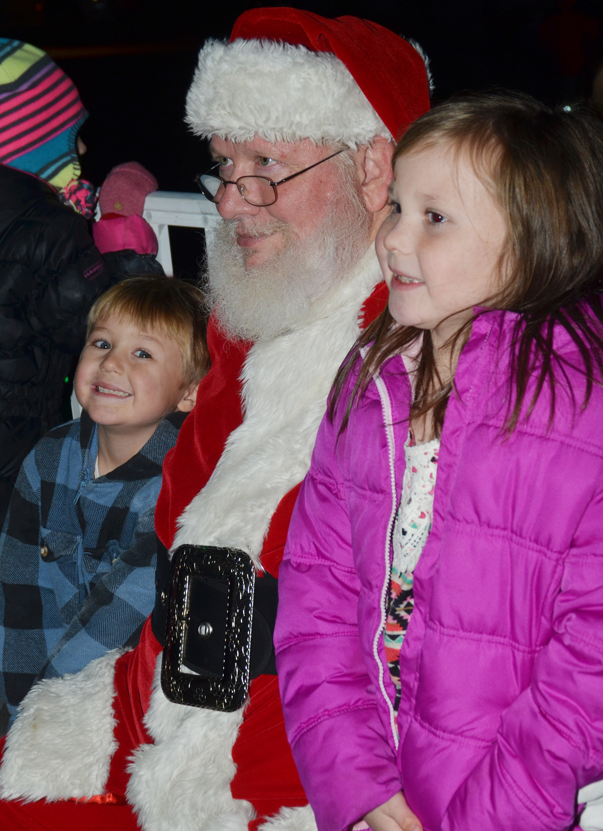 CES second-grader Cadynce Cox, at left, and preschool student Bentley Cox smile for a photo with Santa.