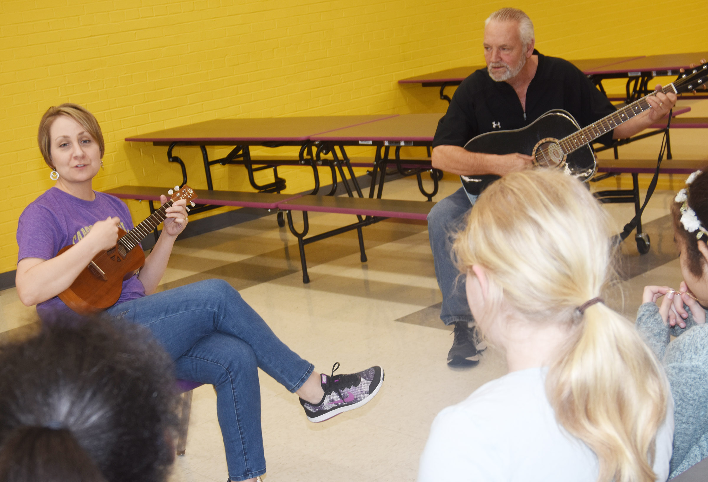CES music teacher Jessica Floyd, at left, plays the ukulele as cafeteria worker Lee Allen plays guitar and choir members sing.