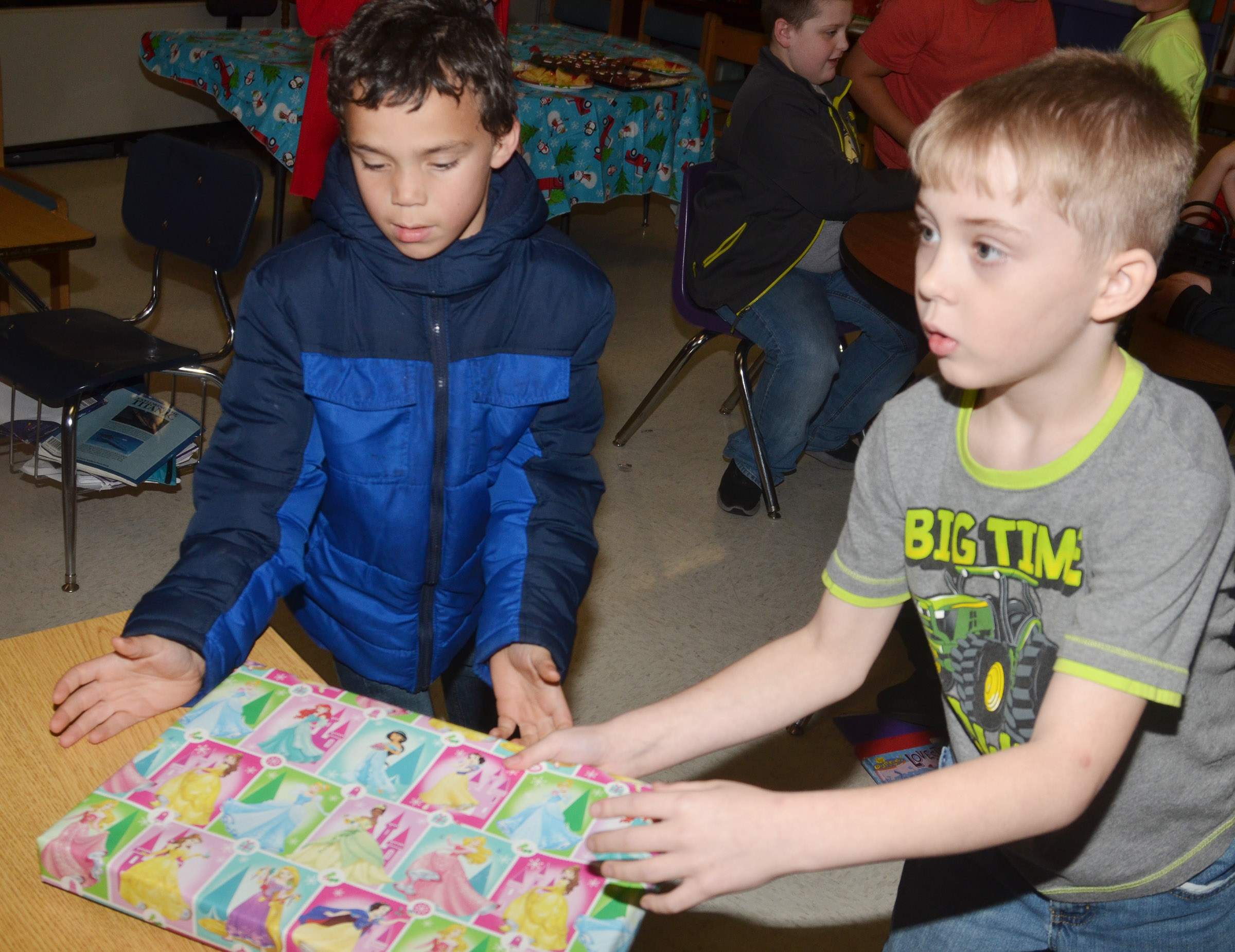 CES third-graders Donnaven Phillips, at left, and Devyn Tingle open a gift that Santa brought for their classroom.