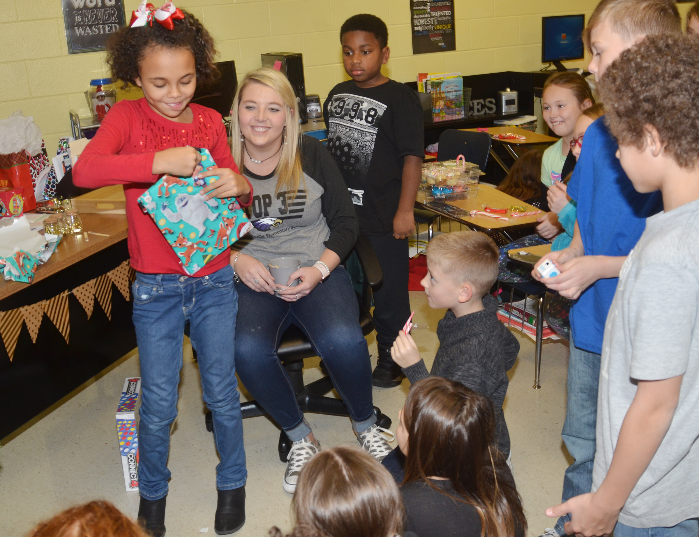 CES third-grader Braelyn Taylor opens a gift that Santa brought for Keri Richard's classroom.