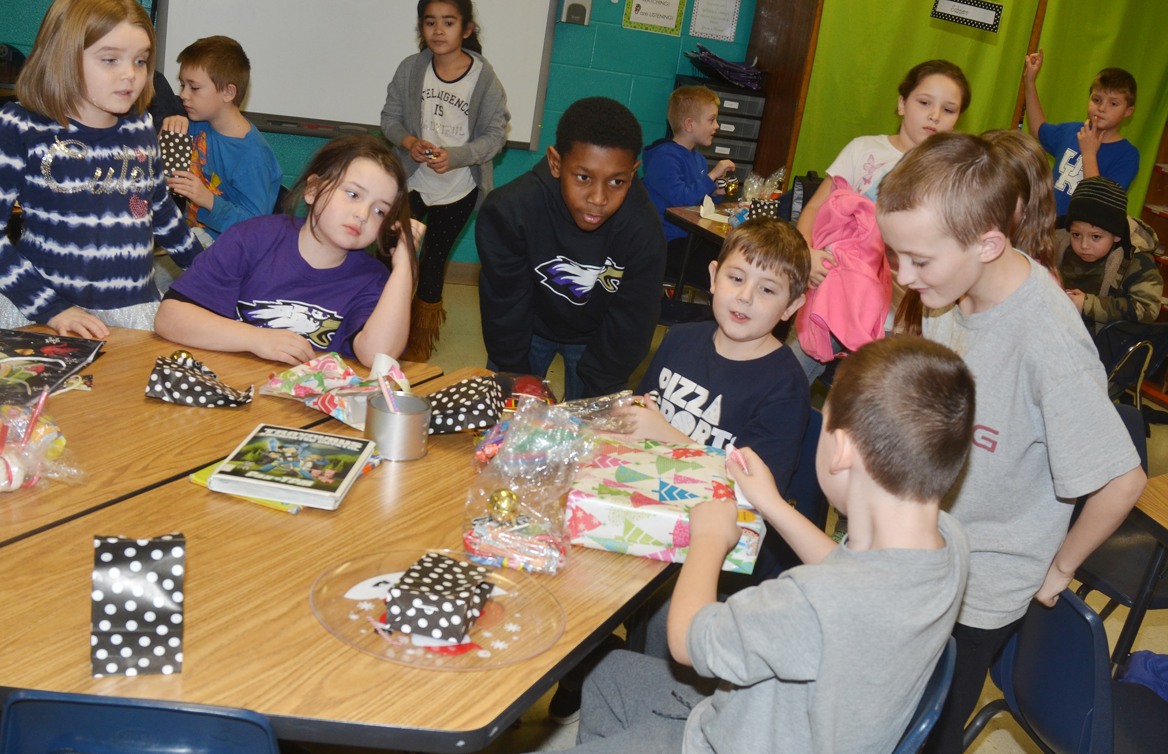CES third-grader Ryan Tungate opens a gift that Santa brought for Hannah Jones's classroom.