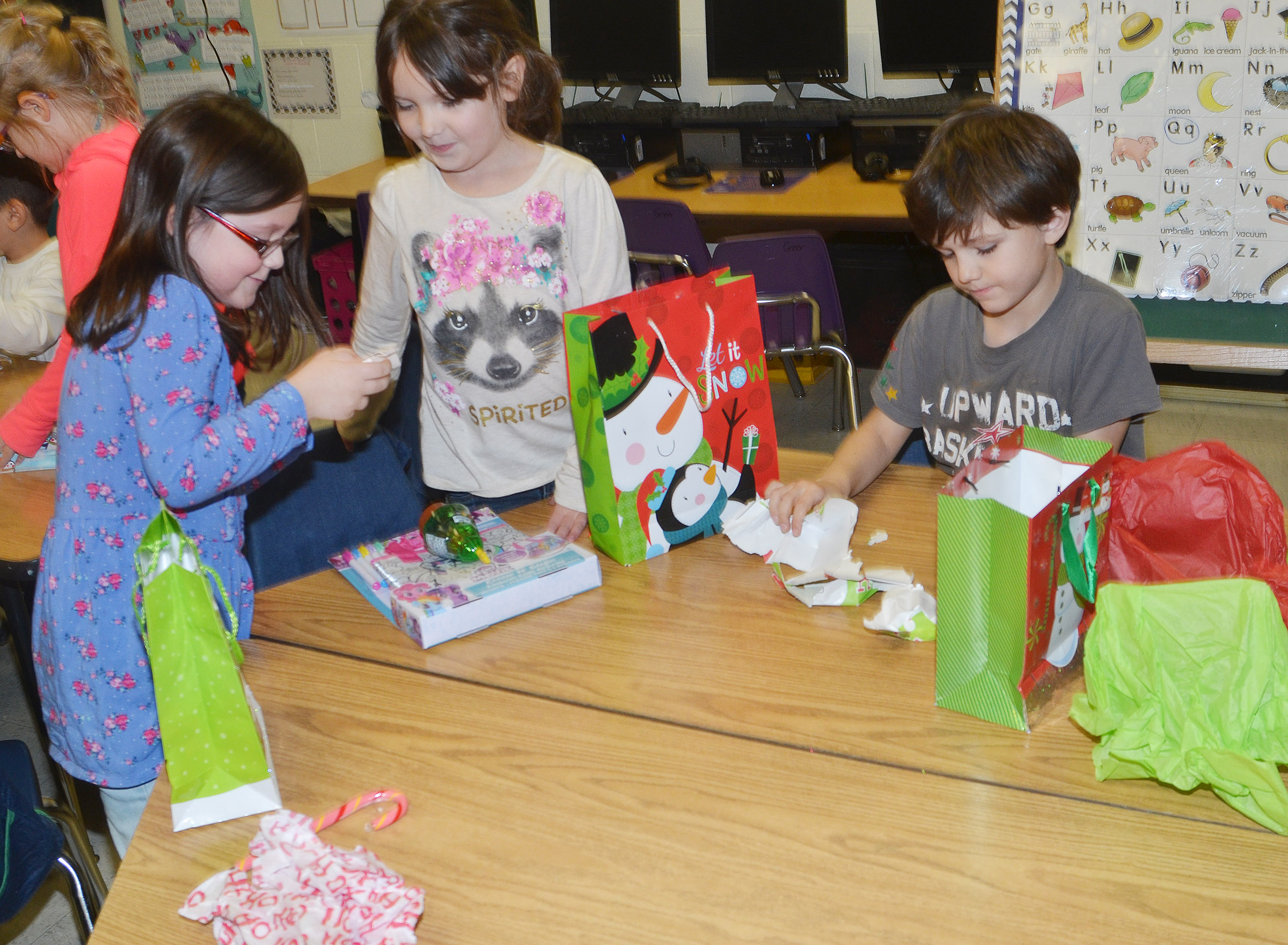 From left, CES first-graders Trinity Clark, Serenity Jones and Aniyah Adams open the presents they received in their class gift exchange.
