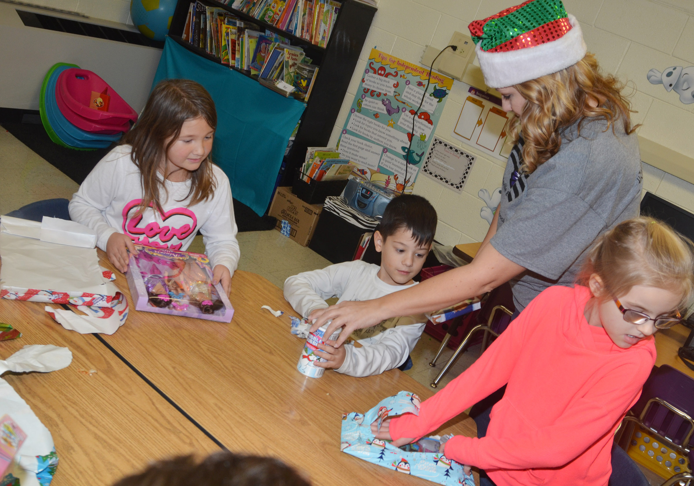 CES first-graders, from left, Destiny Rhinehart, Abram Adkins and Jaden Lutz open presents they received in their gift exchange in Amanda Greer's class.