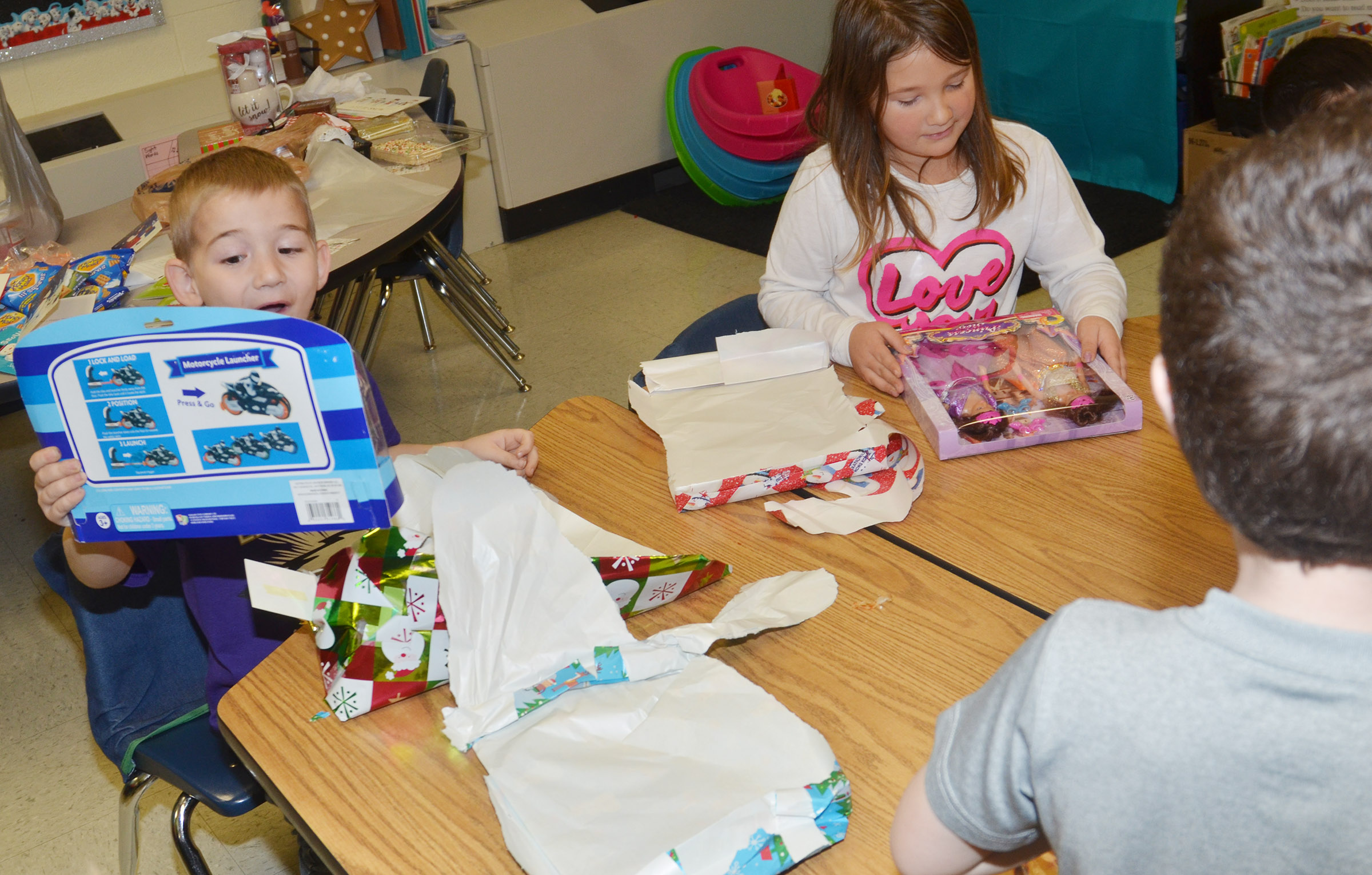 CES first-graders Mason Edwards, at left, and Destiny Rhinehart open presents they received in their class gift exchange.