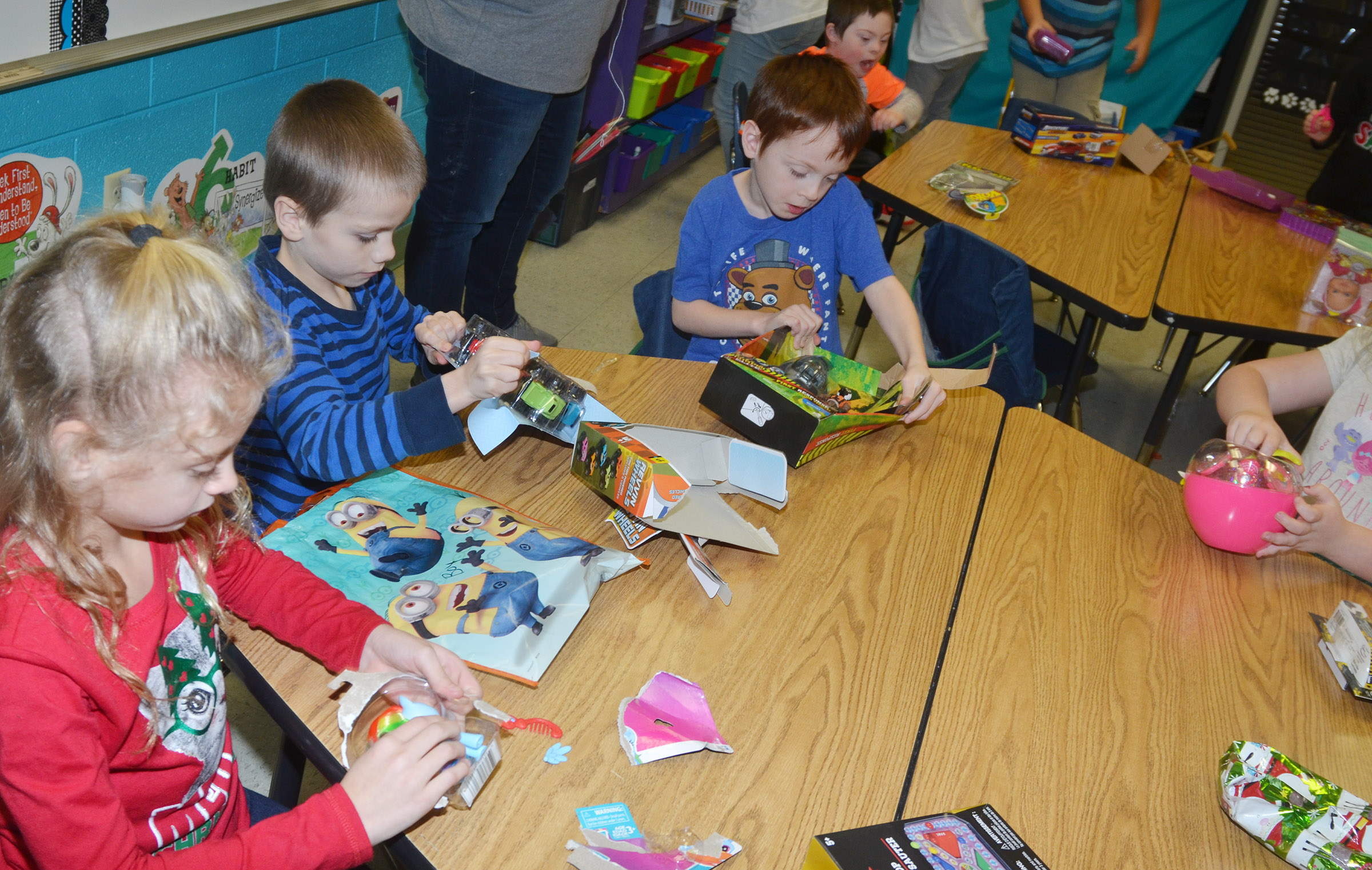 From left, CES second-graders Aliyah Litsey, Alex Eggers and Carson Montes open presents they received in their class gift exchange.