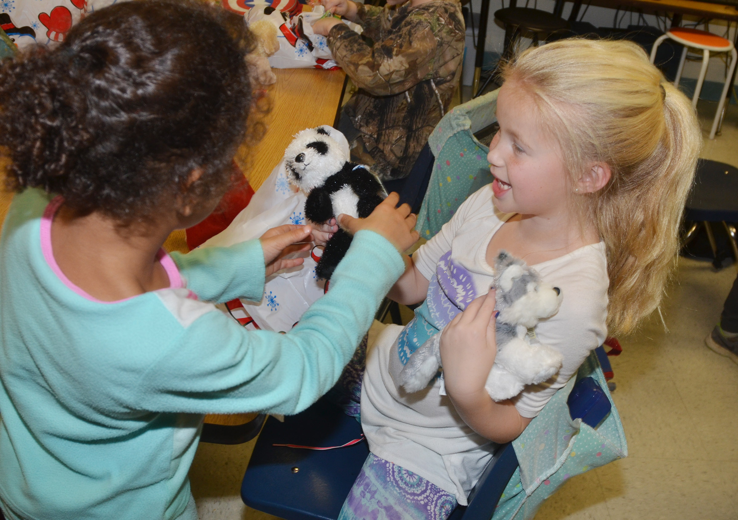 CES first-graders Kylei Thompson, at left, and Lillie Judd show each other the stuffed animals they received from teacher Amanda Barnett.