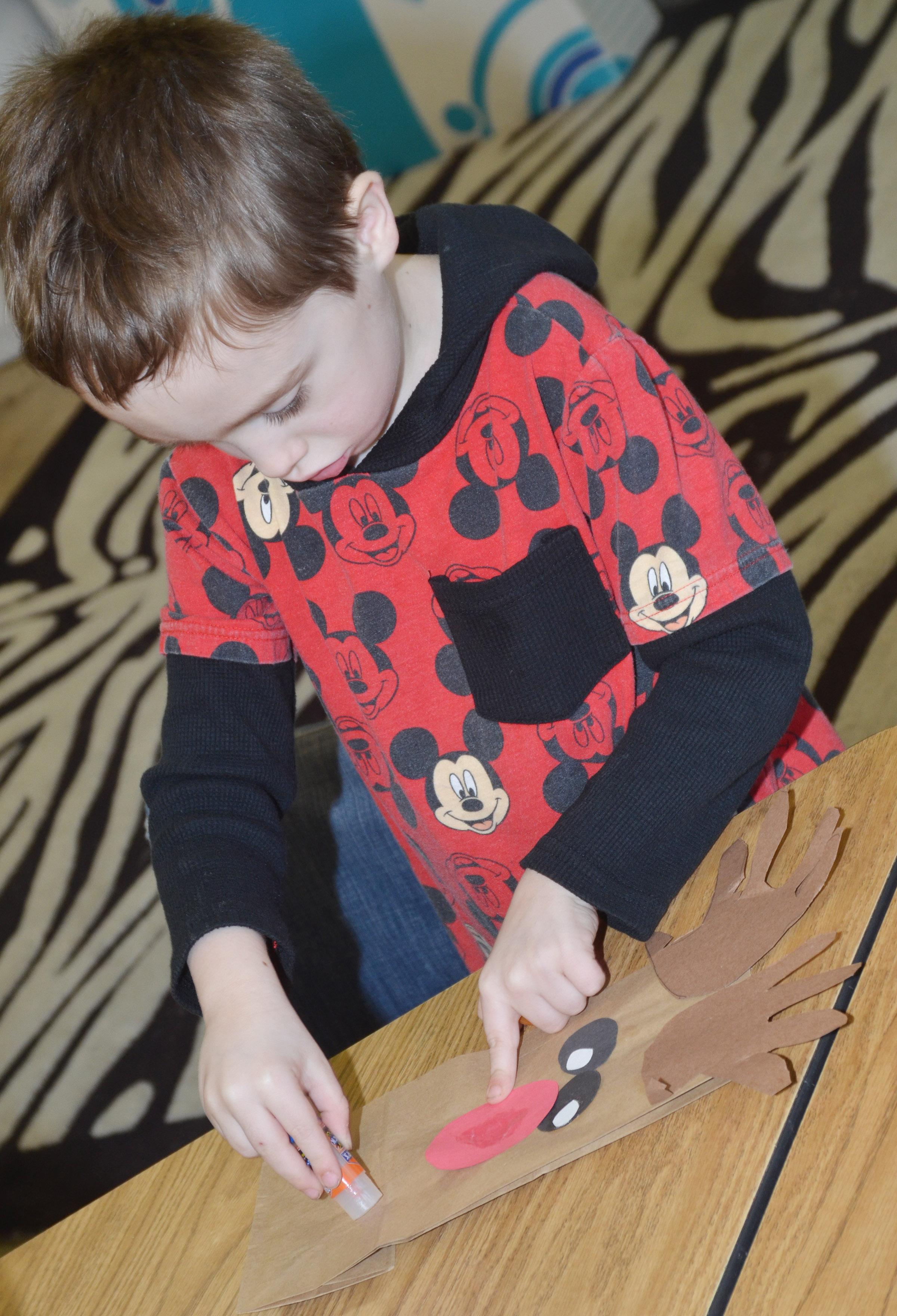CES kindergartener Joshua Dickens makes a reindeer bag to take home his Christmas goodies.