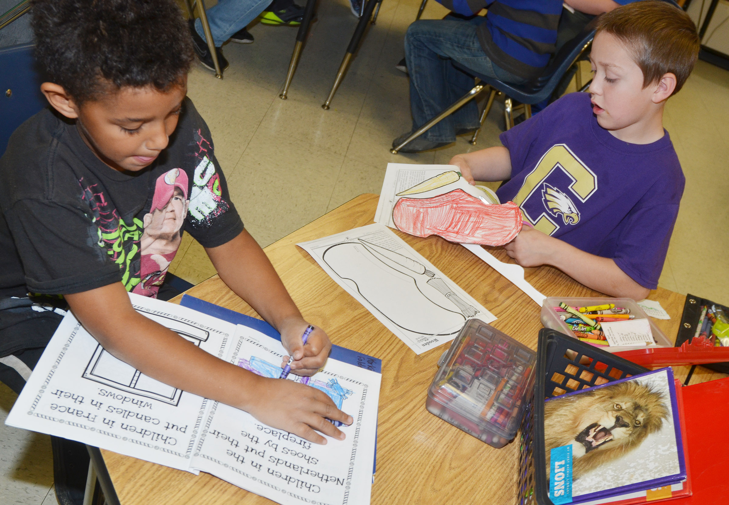 CES second-graders Carter Bell, at left, and Jacob Golden color their worksheets after learning about the holiday traditions in the Netherlands.