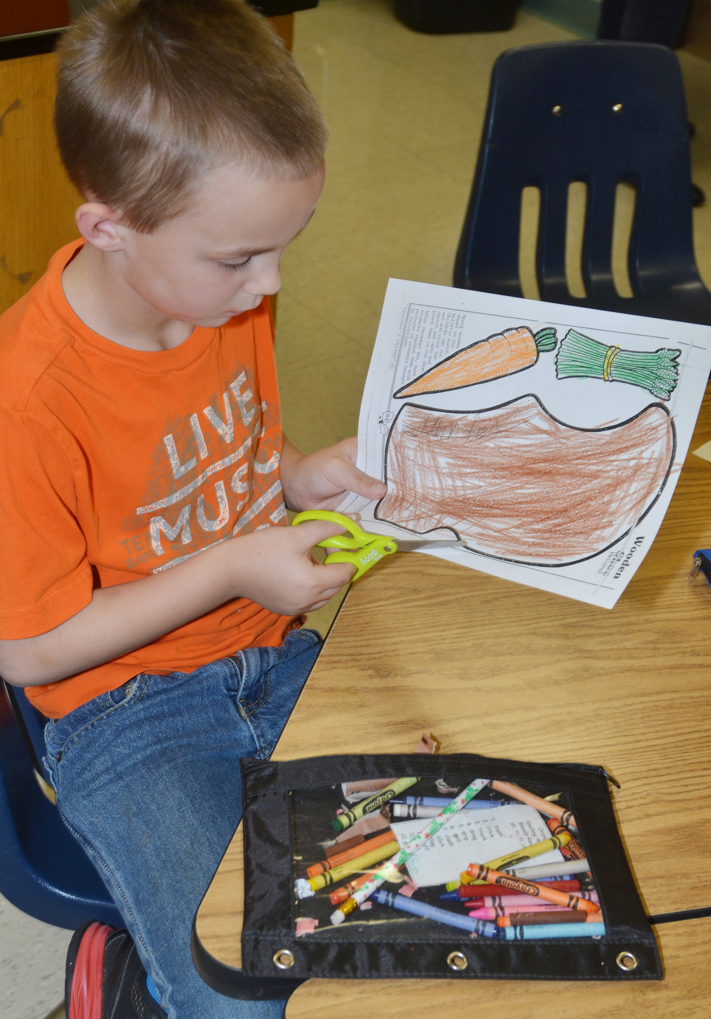CES second-grader Hunter Bates cuts out his wooden shoe and vegetables after learning about the holiday traditions in the Netherlands.